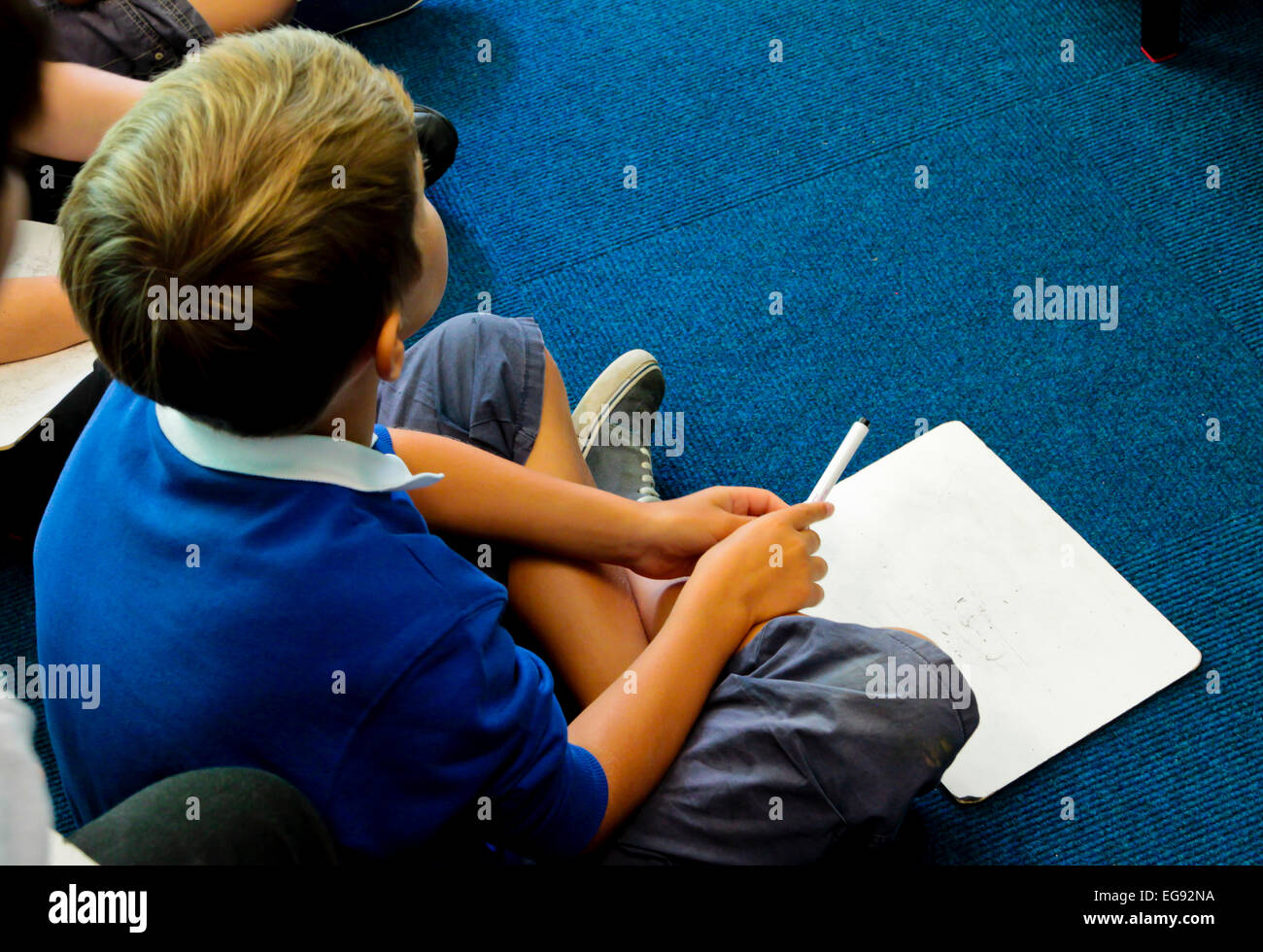 Primary schoolchildren kneeling on the classroom floor during a lesson - Stock Image