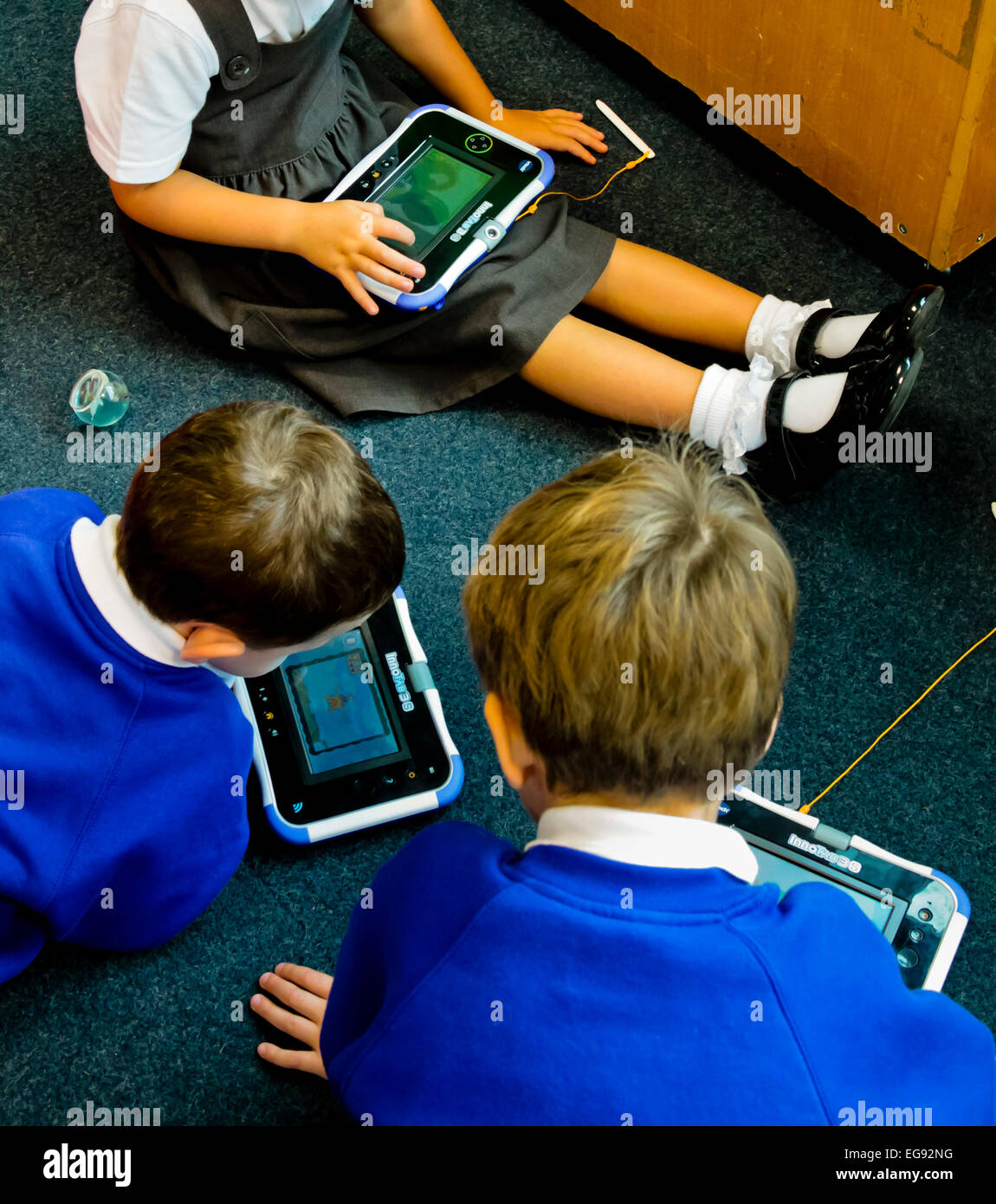 Primary schoolchildren using handheld electronic devices to learn how to read whilst sitting down in a corner of - Stock Image