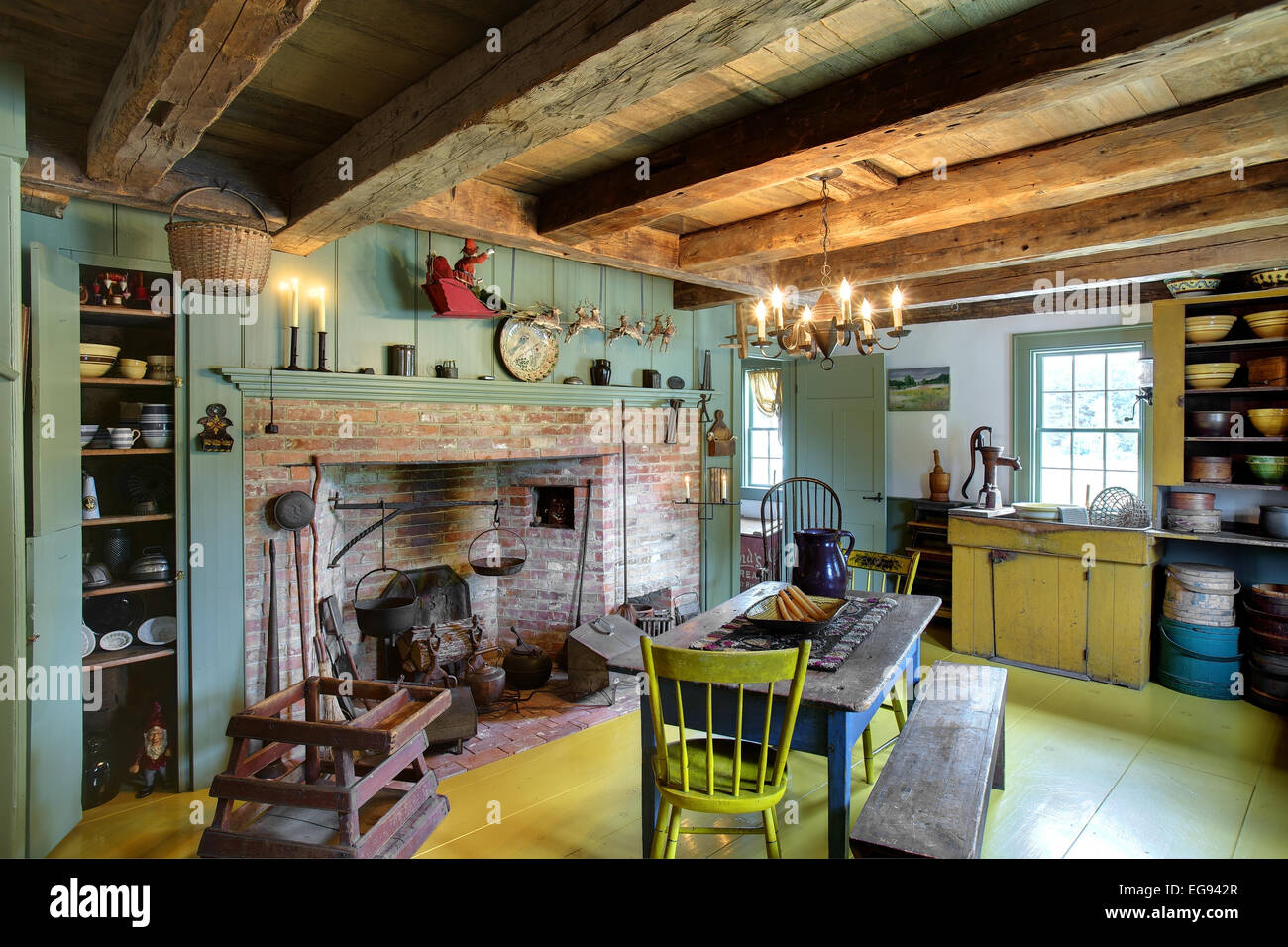 The kitchen, dining room and fireplace in a restored 17th century primitive colonial style home. - Stock Image