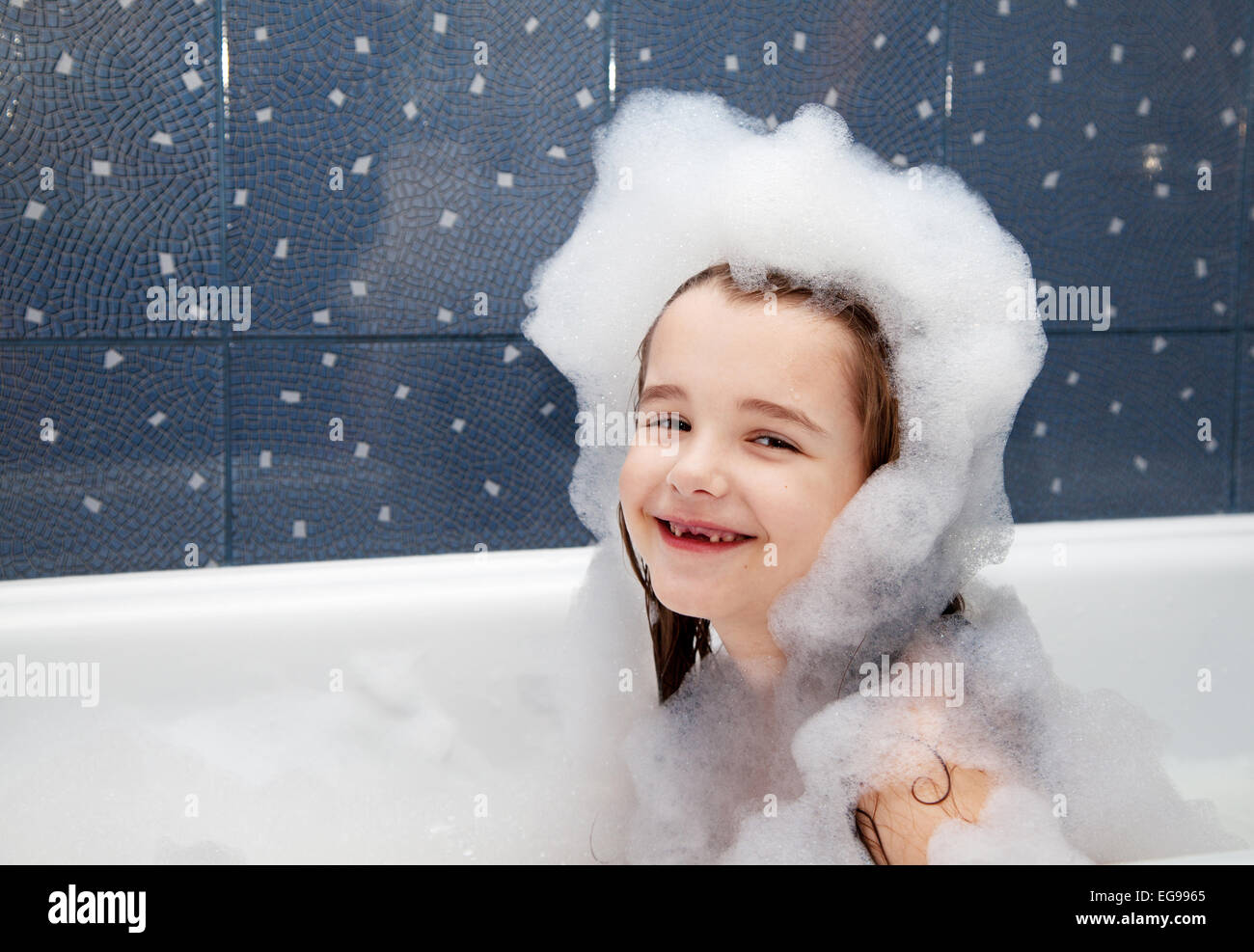 smiling little girl sitting in a bath with soap suds - Stock Image