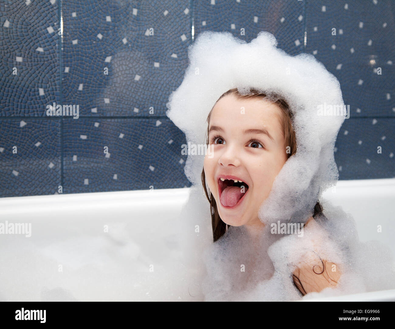surprised little girl sitting in a bath with soap suds - Stock Image