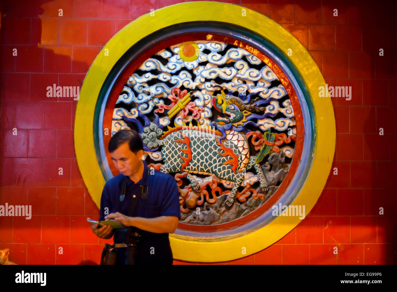 Man stands in front of beautiful rounded wall carvings at Jin De Yuan temple, the oldest Chinese temple in Jakarta, - Stock Image