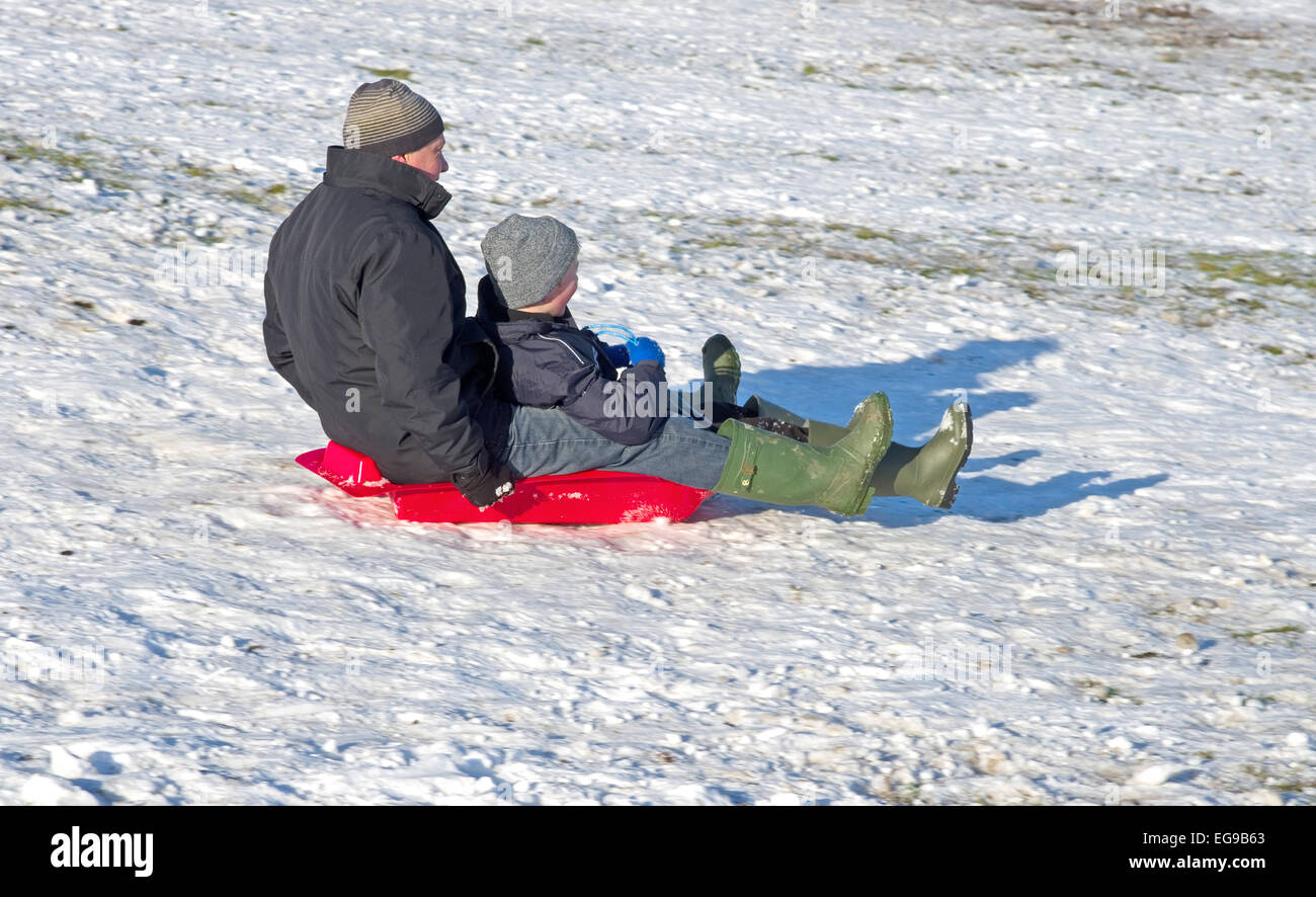 Man and boy on sledge together sledging downhill on snowy hillside Caldbeck fells, Lake District, Cumbria, England - Stock Image