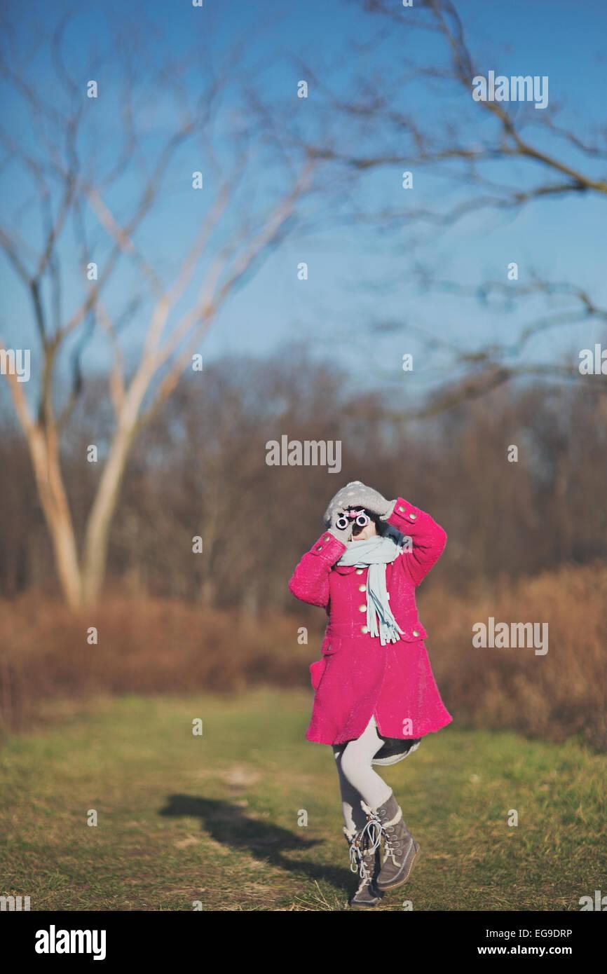 Girl (8-9) looking through binoculars - Stock Image