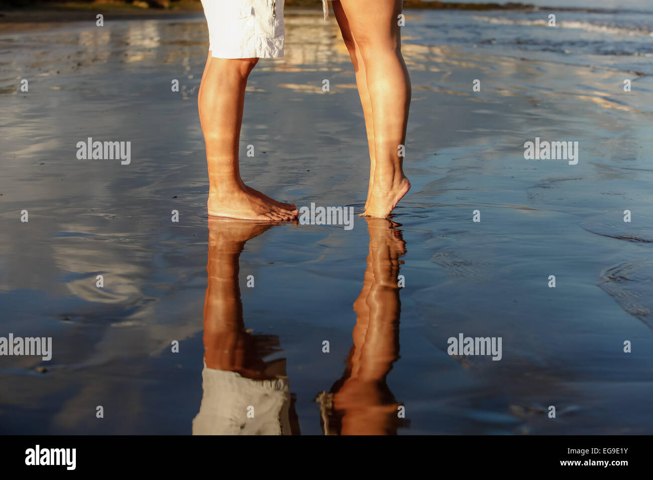 Low-section of young couple standing on beach - Stock Image