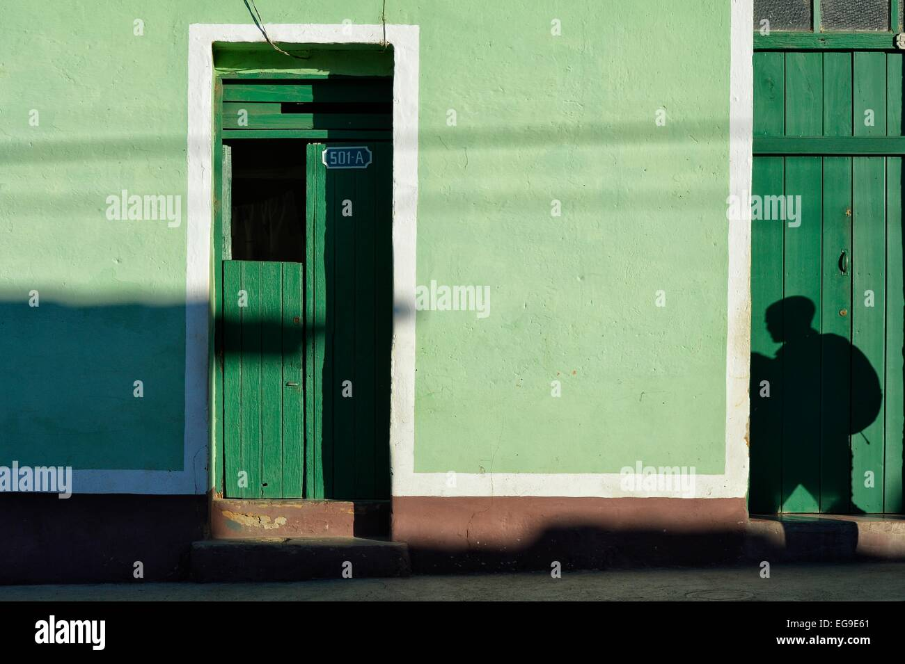 A shadowy figure seen a bright green painted wall in Trinidad, Cuba - Stock Image