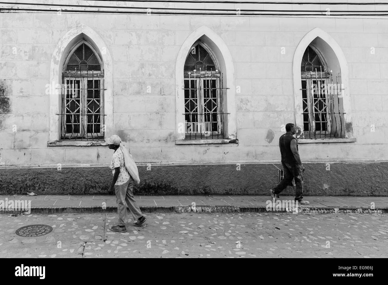 Two Cuban people walk past a building with three arched windows. - Stock Image