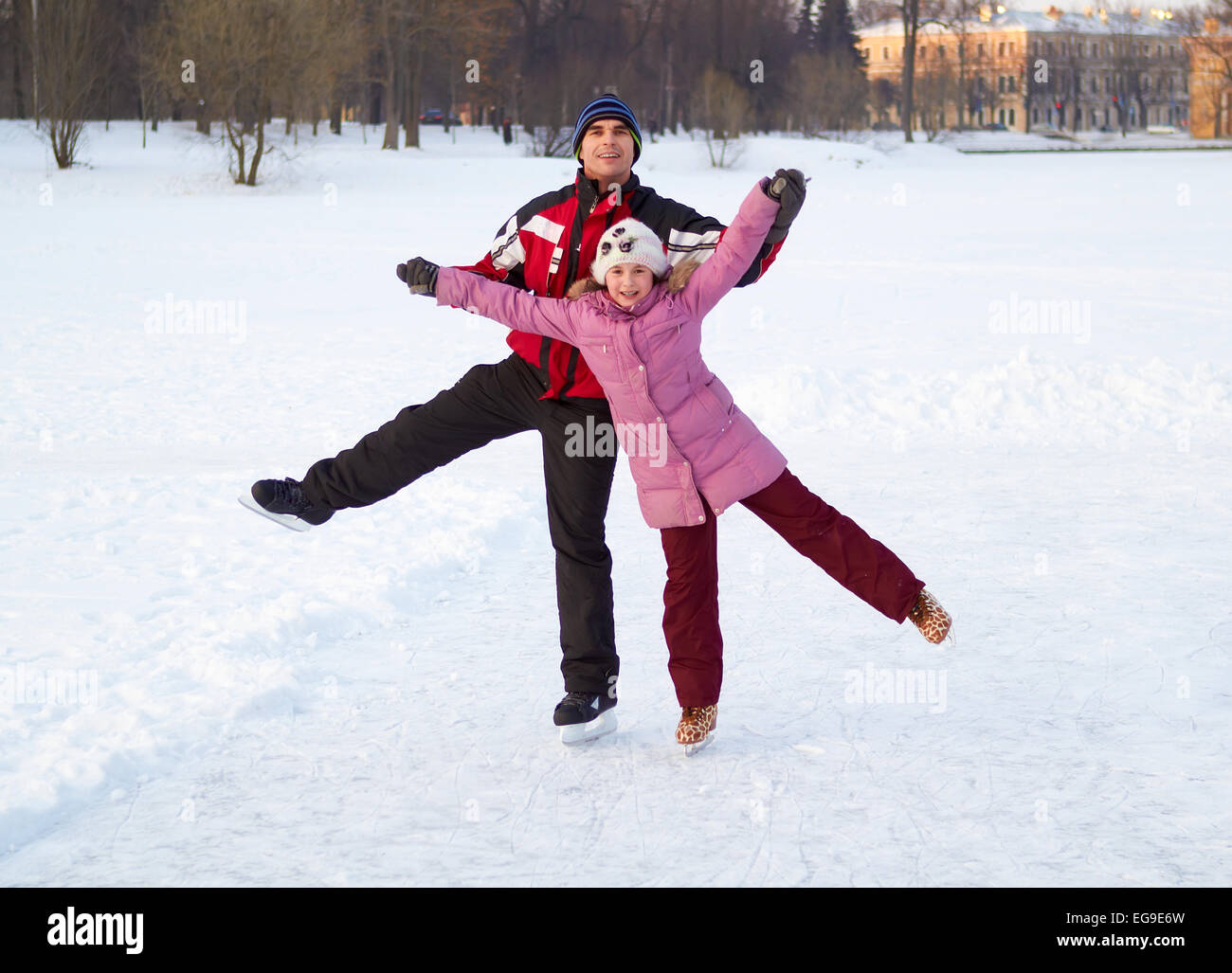 Happy family on skating rink outdoors - Stock Image