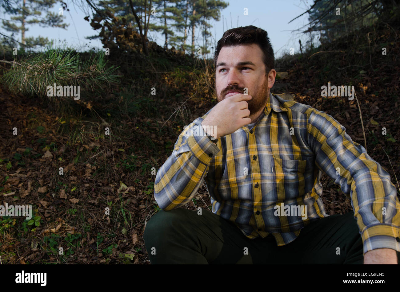 Young man contemplating in forest - Stock Image