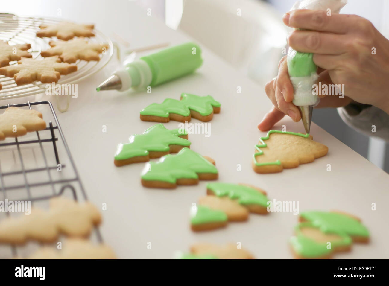 Woman decorating cookies with green colored icing - Stock Image