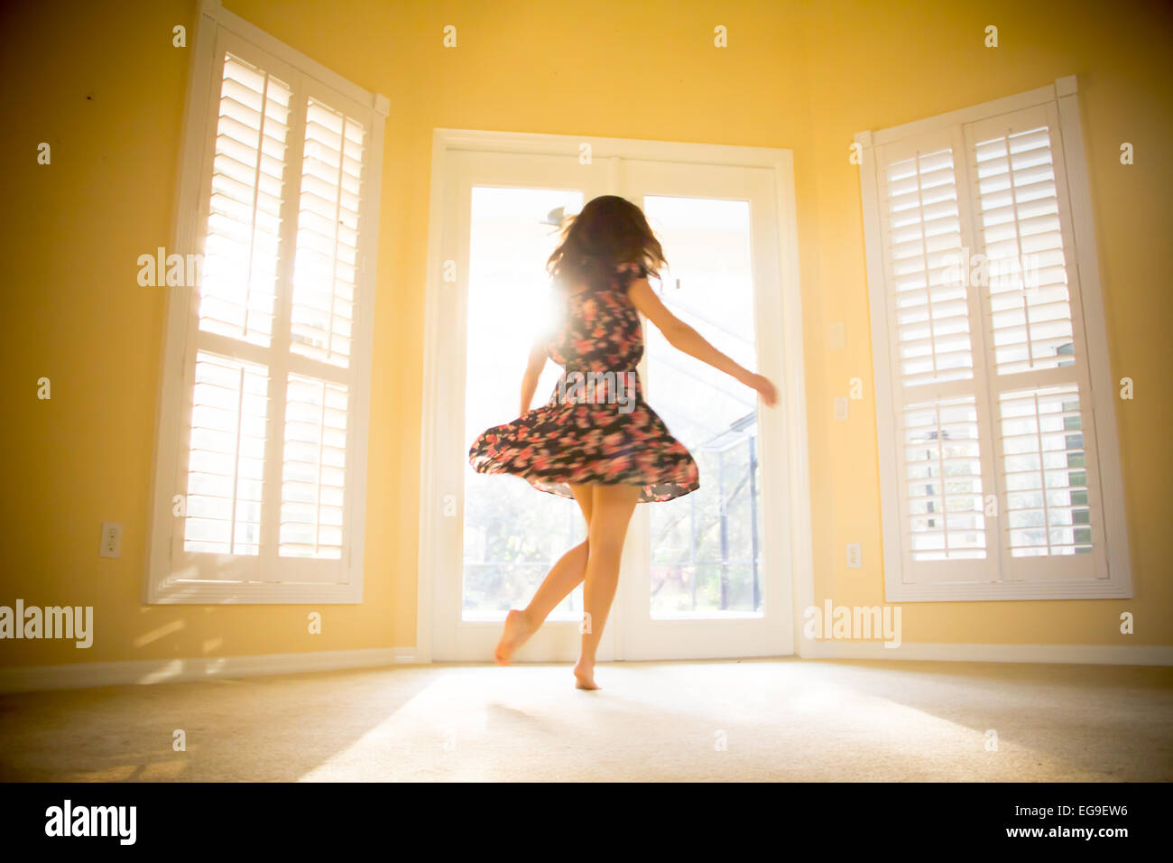 Young woman spinning in sunny room - Stock Image