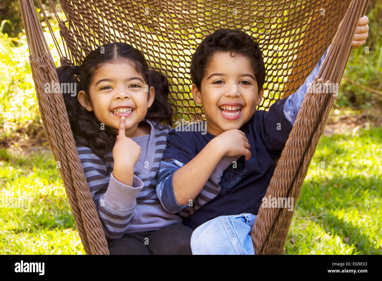 Twin brother and sister sitting in a hammock pulling funny faces Stock Photo