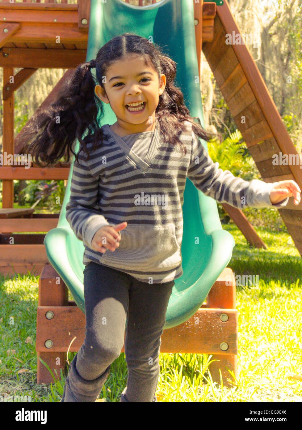 Happy girl getting off slide - Stock Image