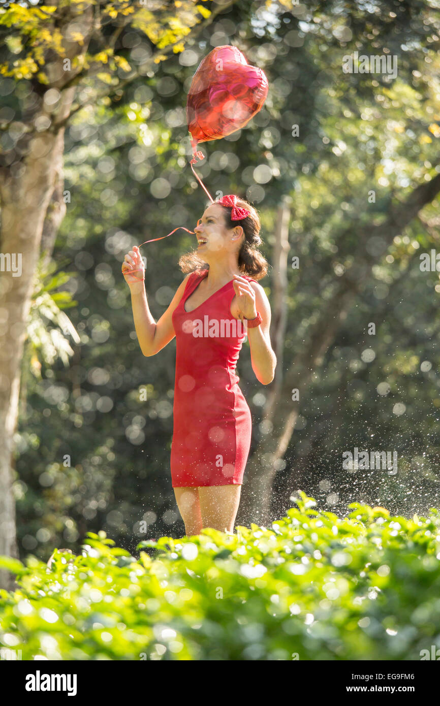 Woman with red heart shape balloon in a park - Stock Image