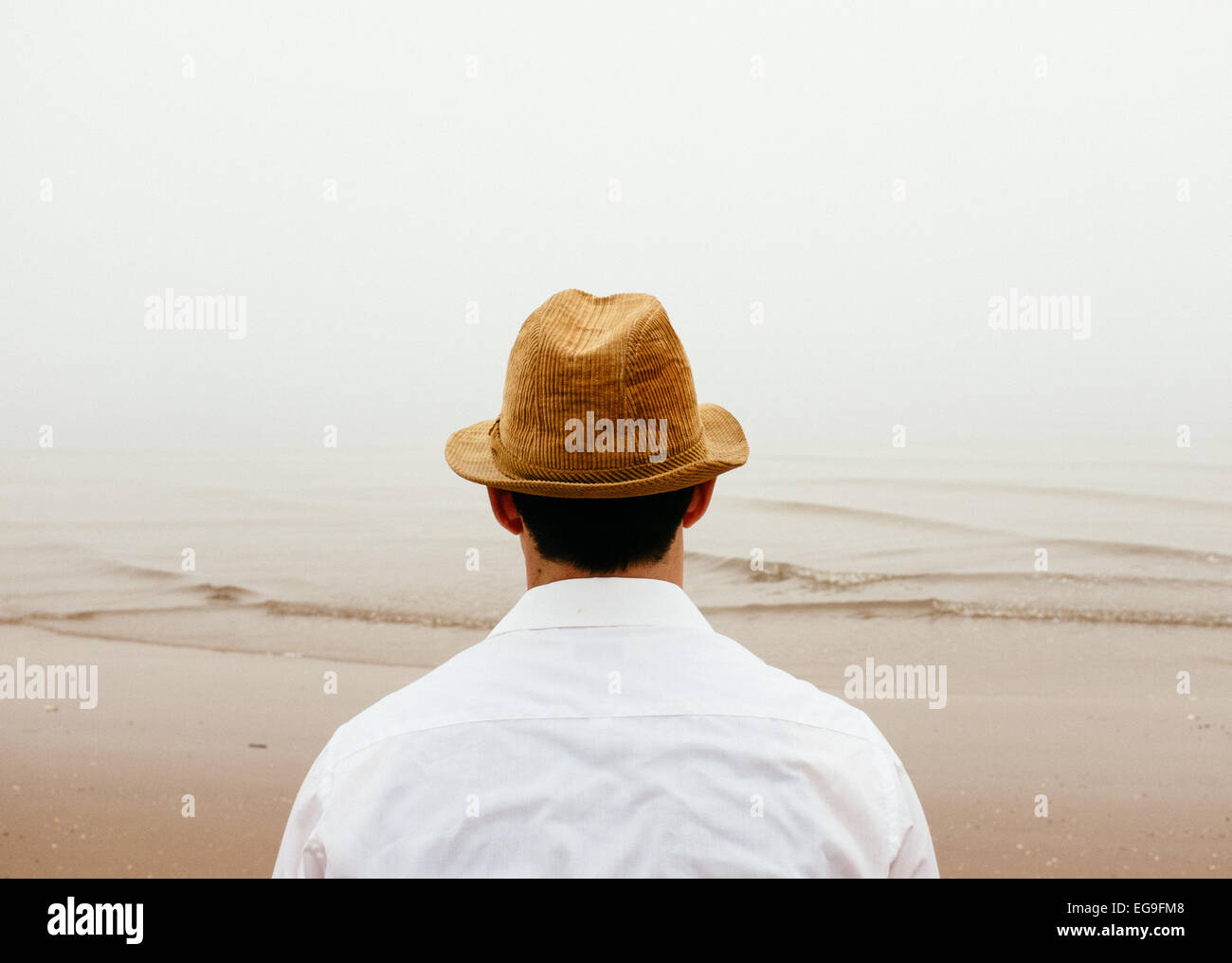 Man in straw hat on beach looking at view - Stock Image