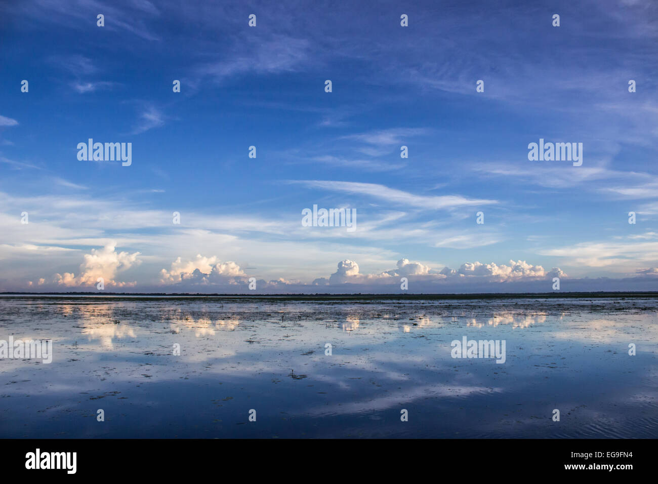 Bangladesh, Sunamgonj, Cumulus clouds reflecting in water - Stock Image