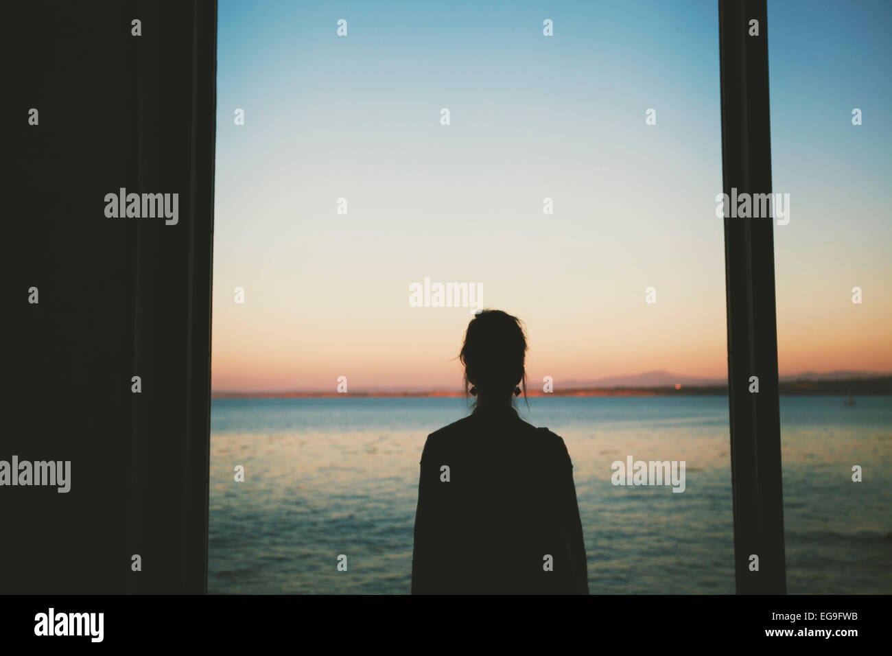 Woman looking at sea through window - Stock Image