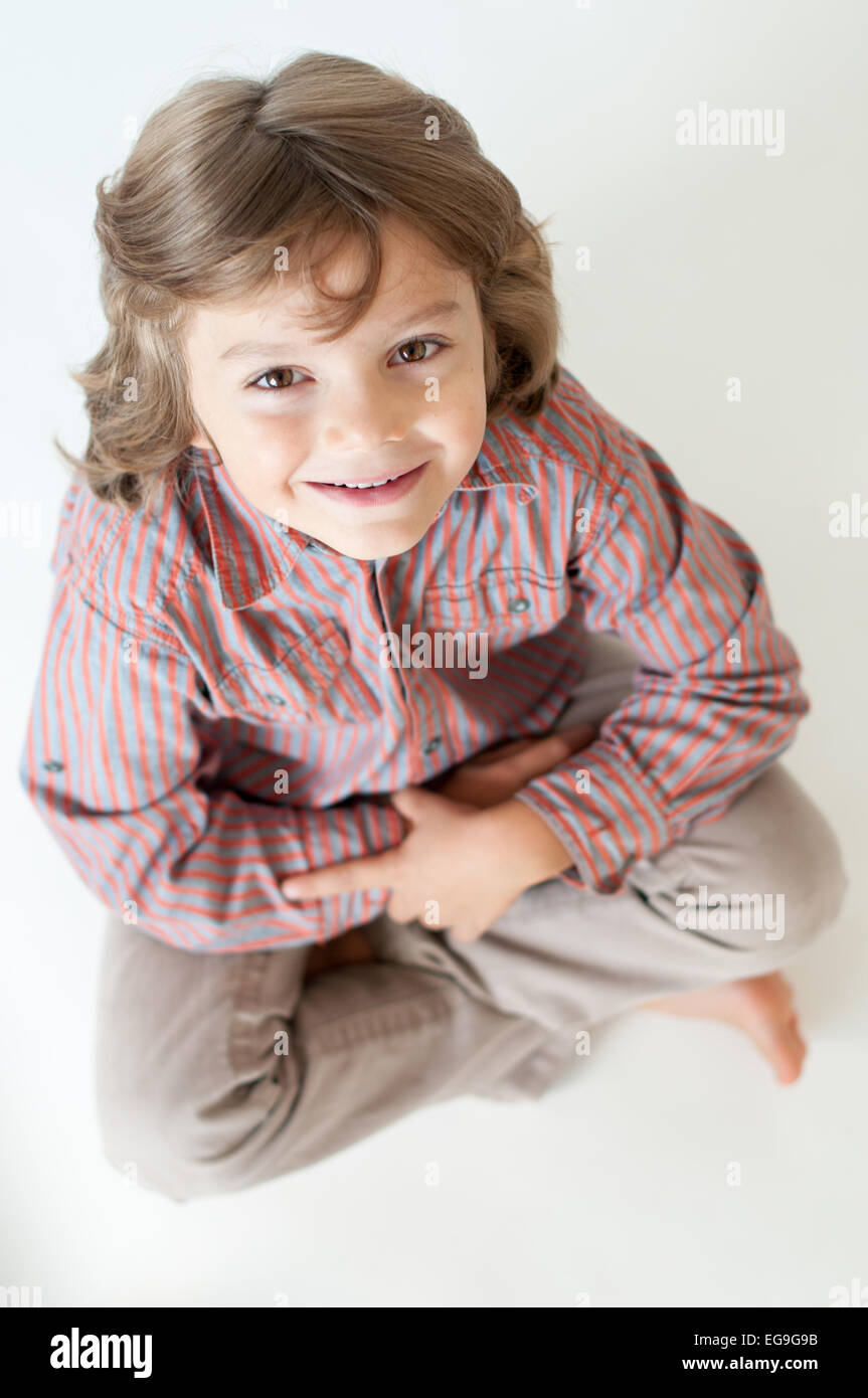 Boy (6-7) sitting cross-legged looking up - Stock Image