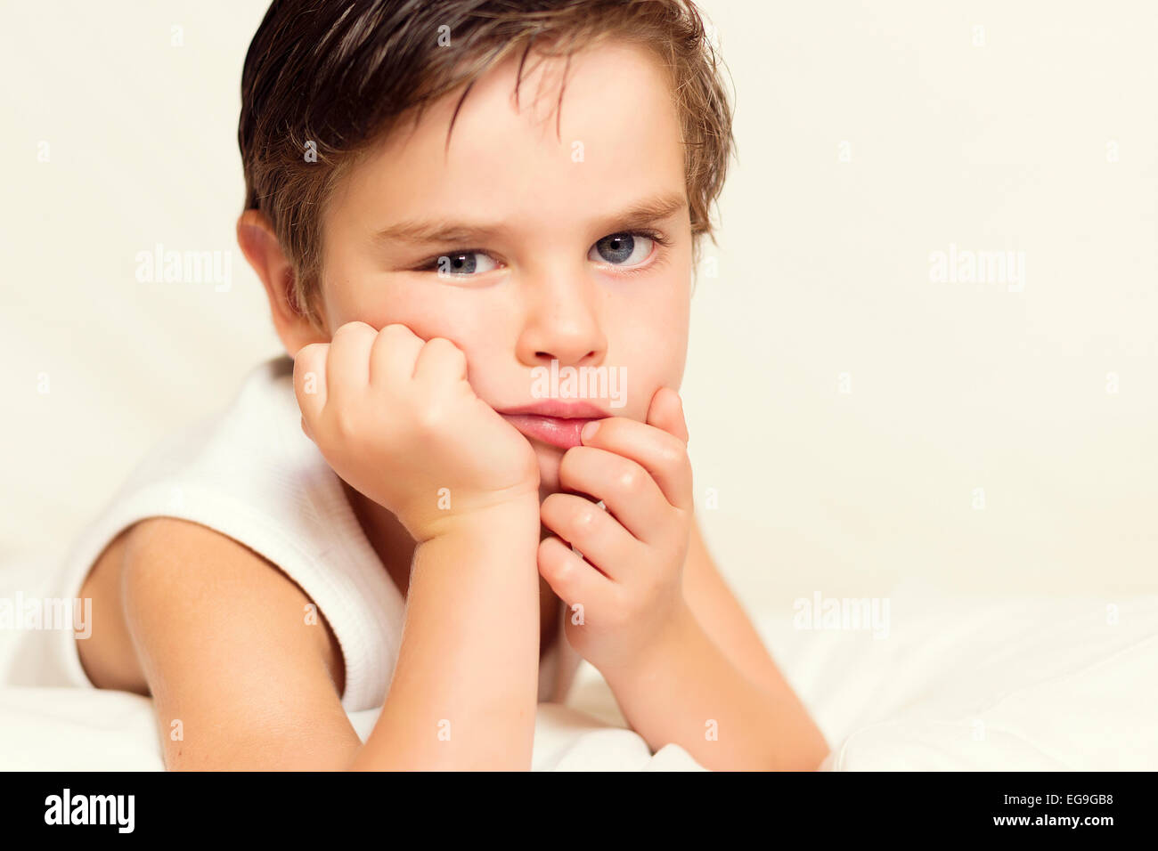 Portrait of boy with hand on chin - Stock Image