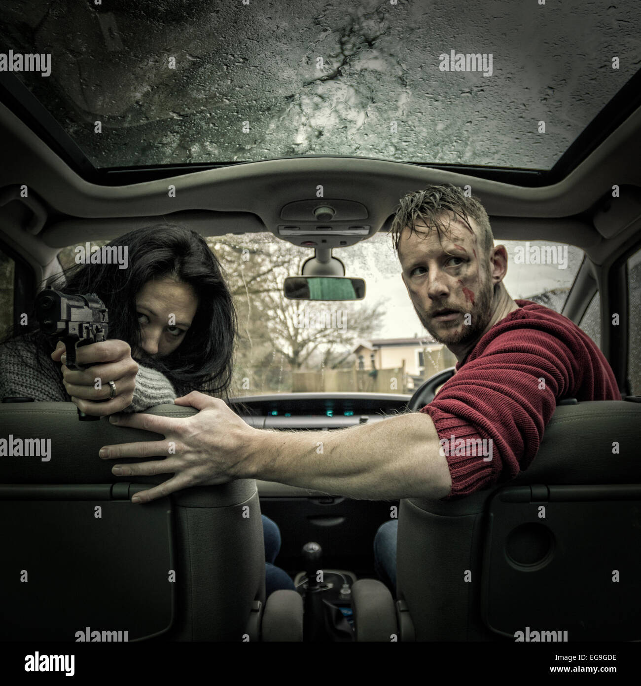 Couple in car with gun Stock Photo