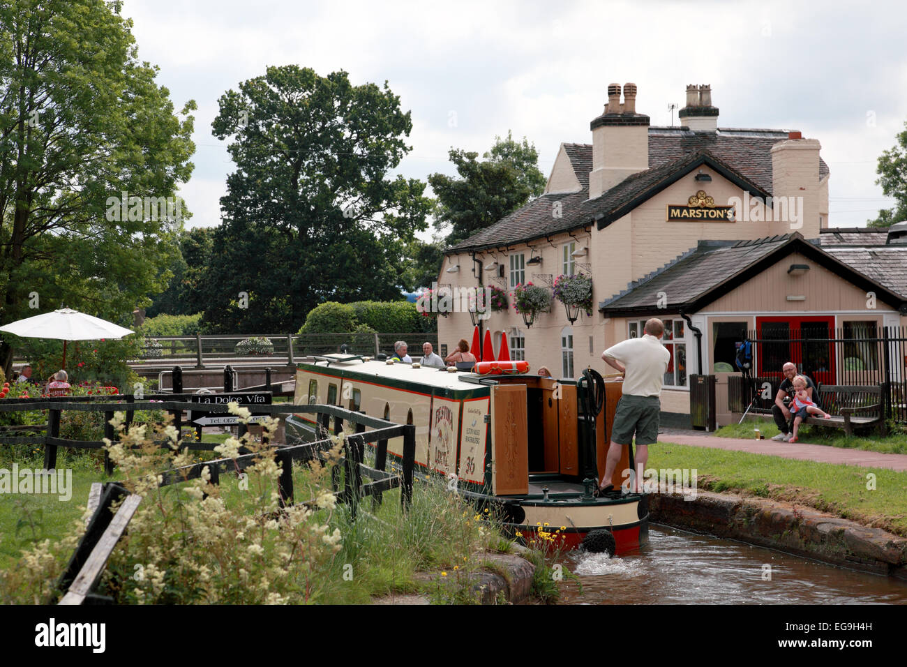 A narrowboat entering the Star Lock on the Trent and Mersey Canal next to the Star Inn at Stone in Staffordshire - Stock Image