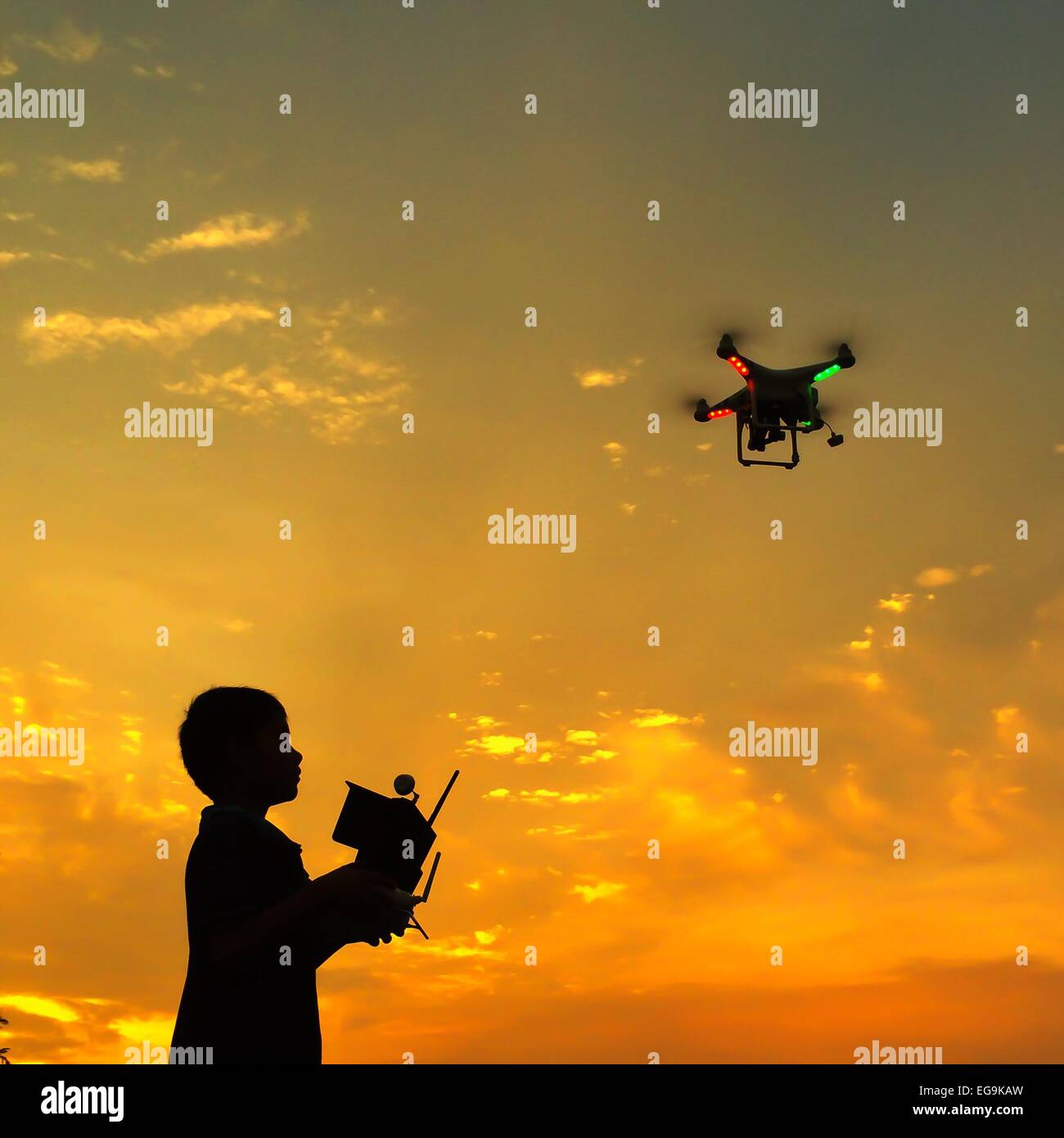 Silhouette of boy Flying a drone at sunset - Stock Image