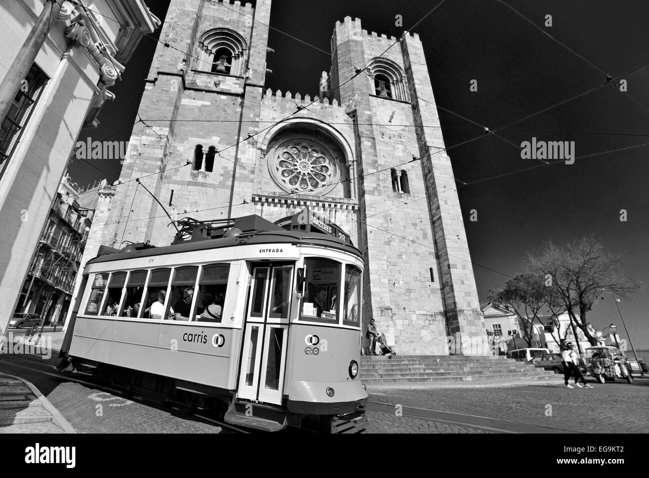 Portugal, Lisbon: Historic tram with tourists passing the medieval Cathedral in the Alfama as black and white version - Stock Image