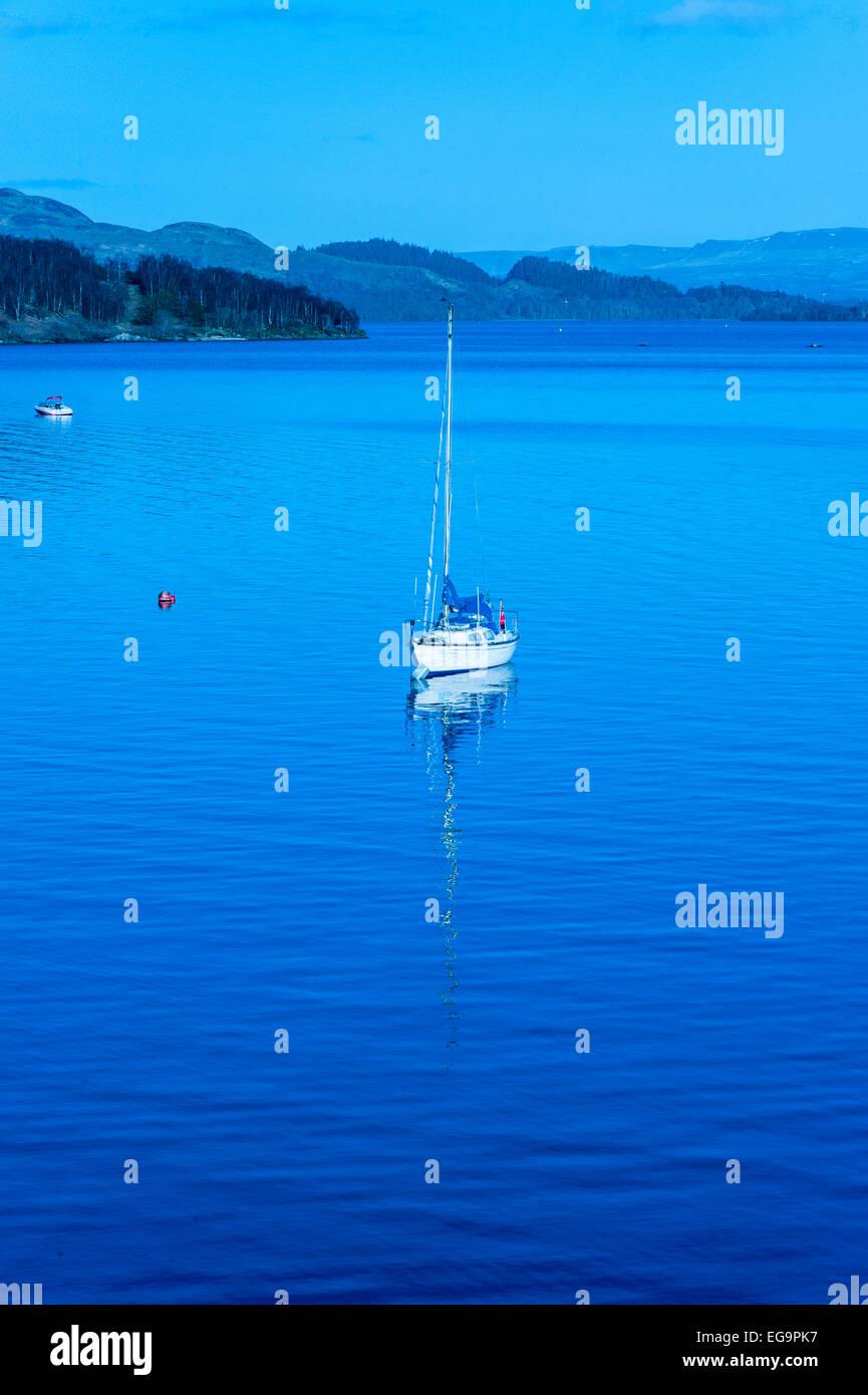 Single sailing boat on Loch Lomond at dusk - Stock Image