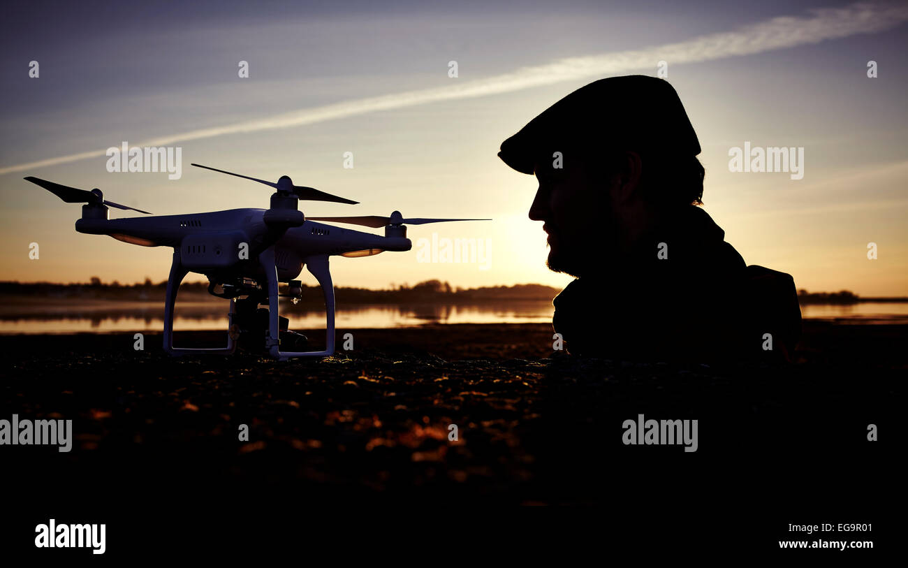 Silhouetted man at sunset with a quadcopter drone - Stock Image