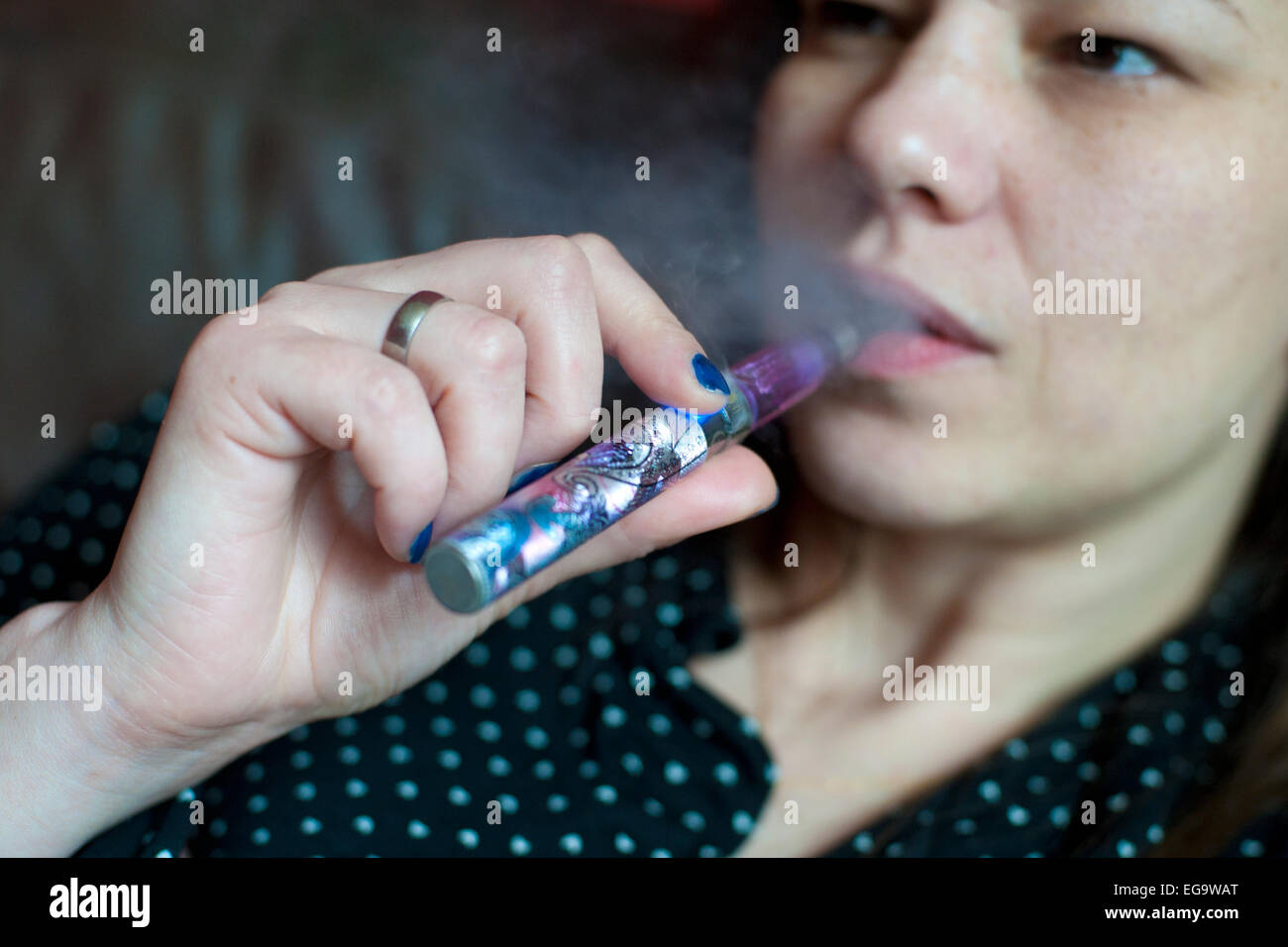 a woman relaxing smoking an e cigarette and blowing out vapour - Stock Image