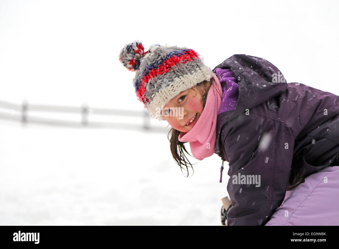 3f0e895c8c0d3 pretty little girl with wool beret playing on snow in the mountains - Stock  Image