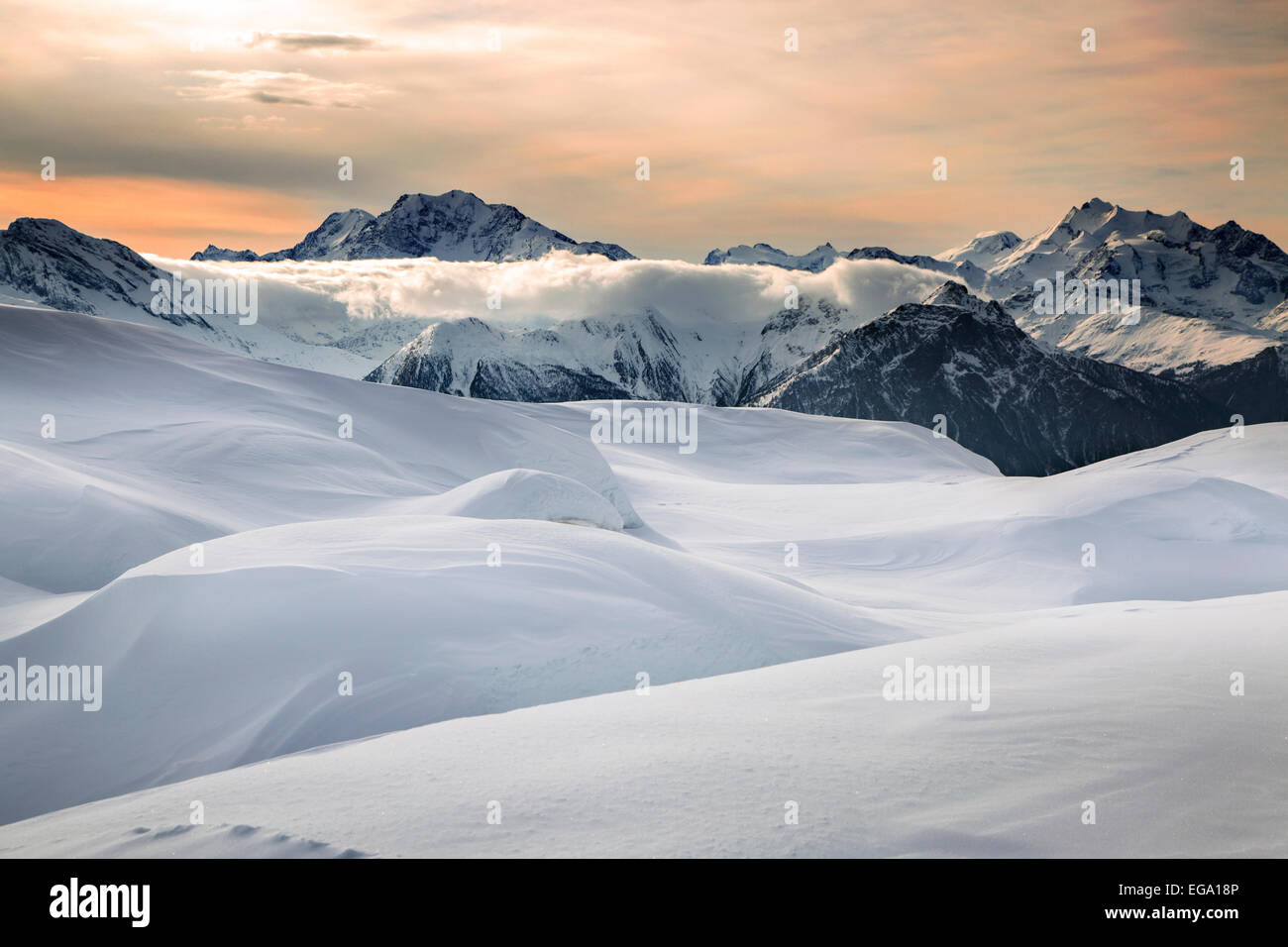 Sunset over snow covered Alpine mountains in winter in the Swiss Alps at Wallis / Valais, Switzerland - Stock Image