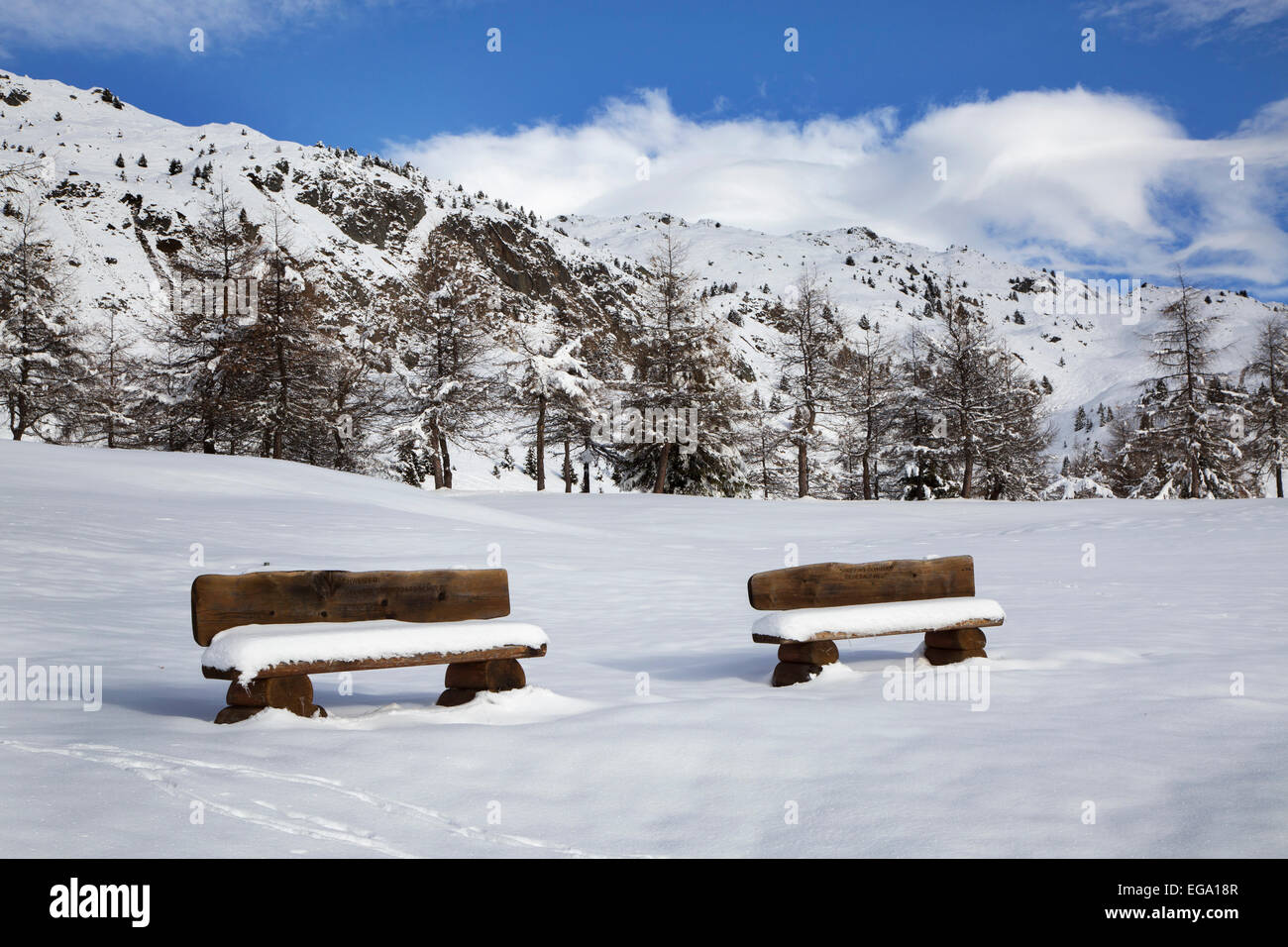 Two snow covered wooden benches at the village Riederalp in winter, Wallis / Valais, Switzerland - Stock Image