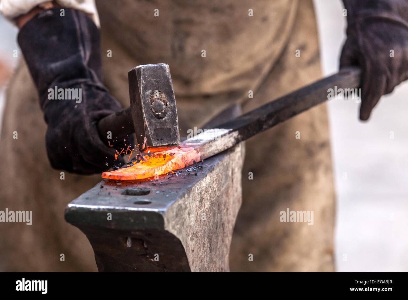 Blacksmith anvil and hammer at work - Stock Image