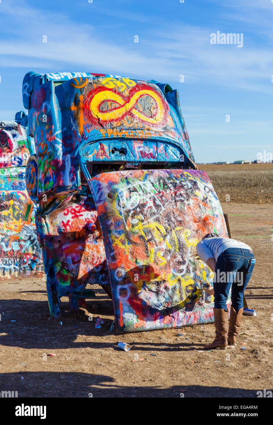 Young woman spray painting a car at the Cadillac Ranch, a public art