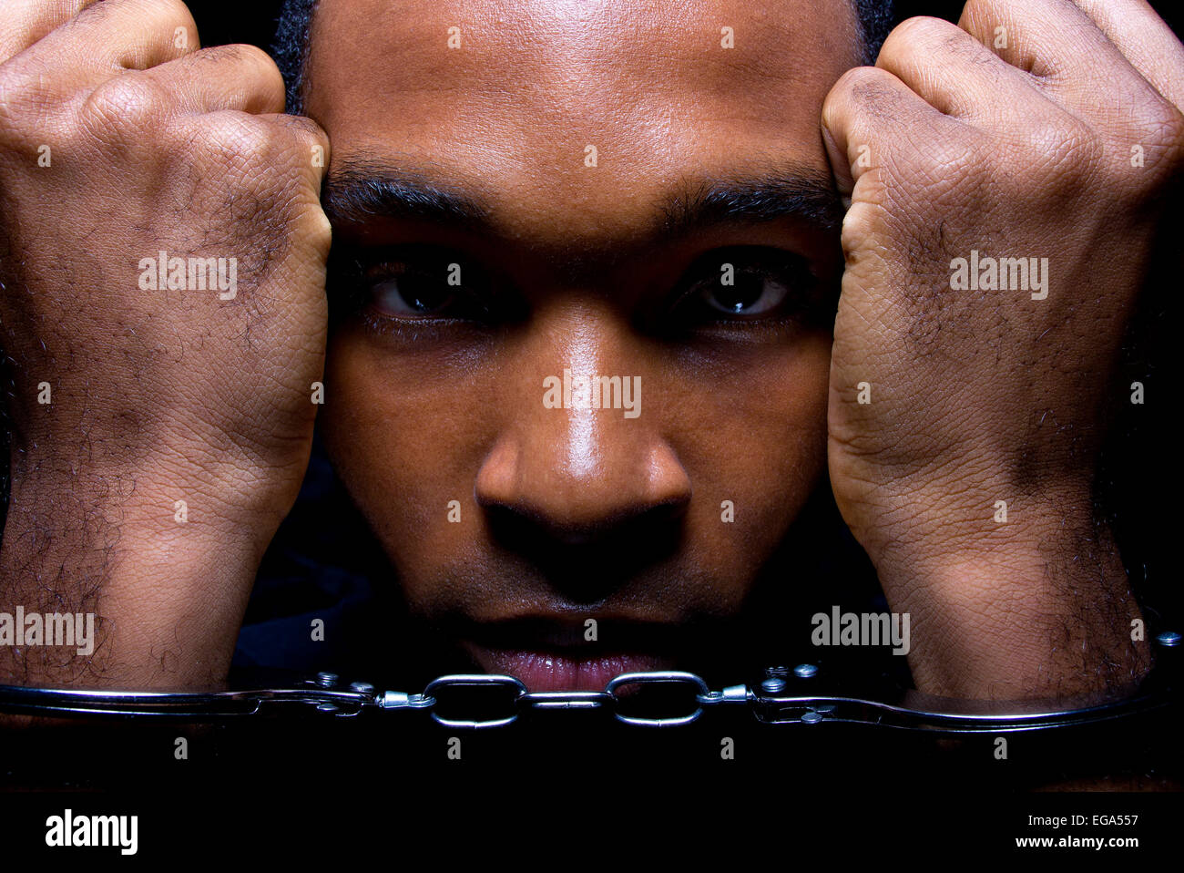 close up portrait of hand cuffed black man - Stock Image