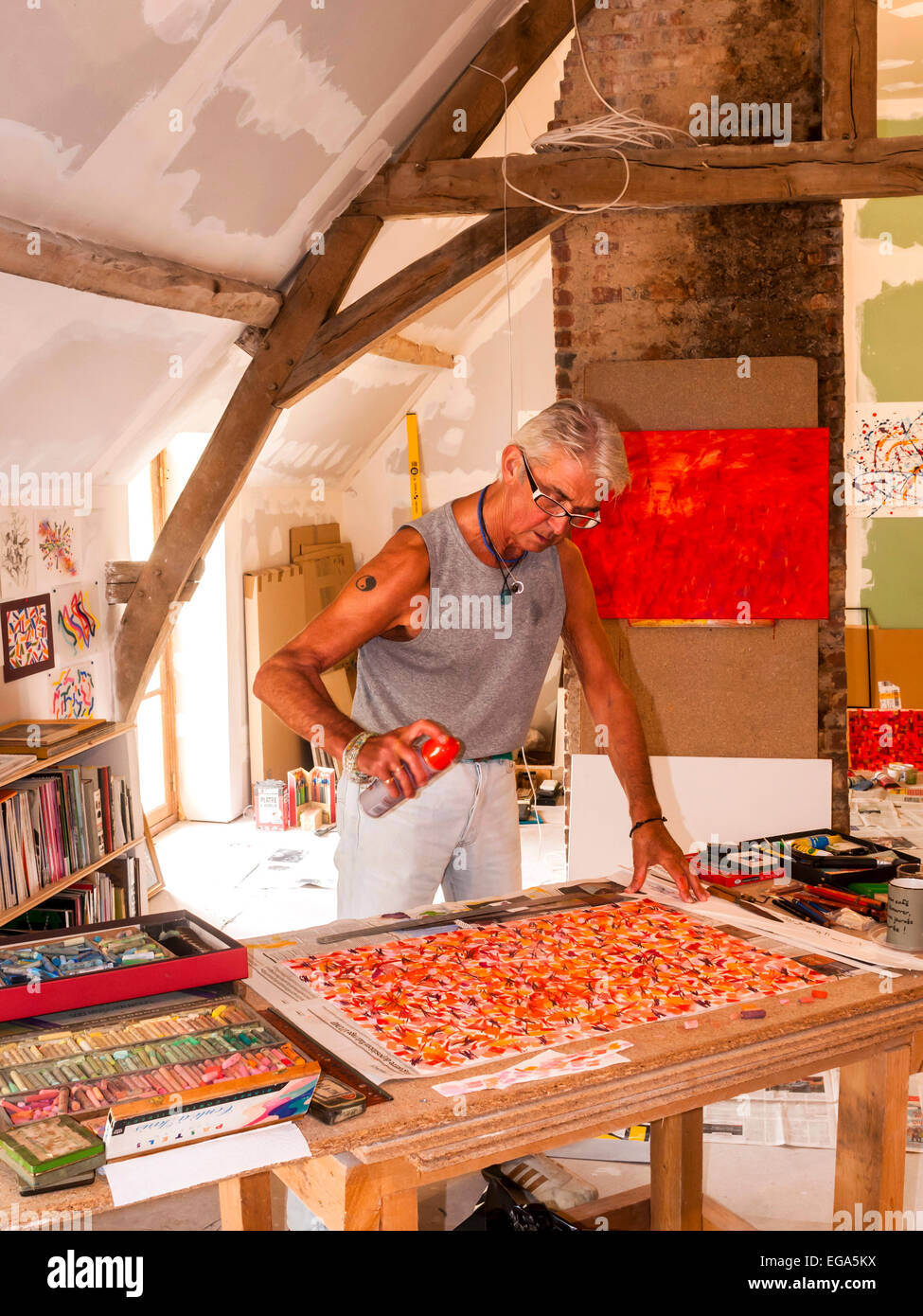 Artist Ed Buziak creating an abstract artwork with pastel crayons - France. - Stock Image