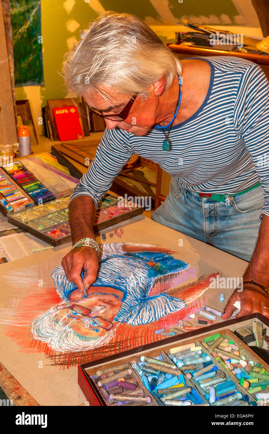Artist Ed Buziak drawing a self-portrait with coloured pastel crayons - France. - Stock Image