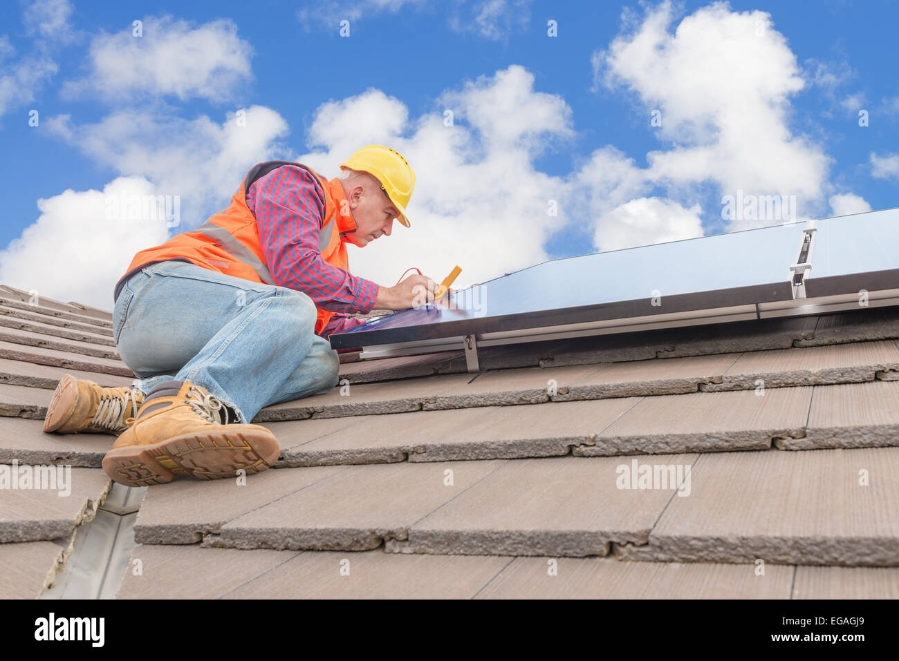 experienced worker checking solar panels on house roof - Stock Image