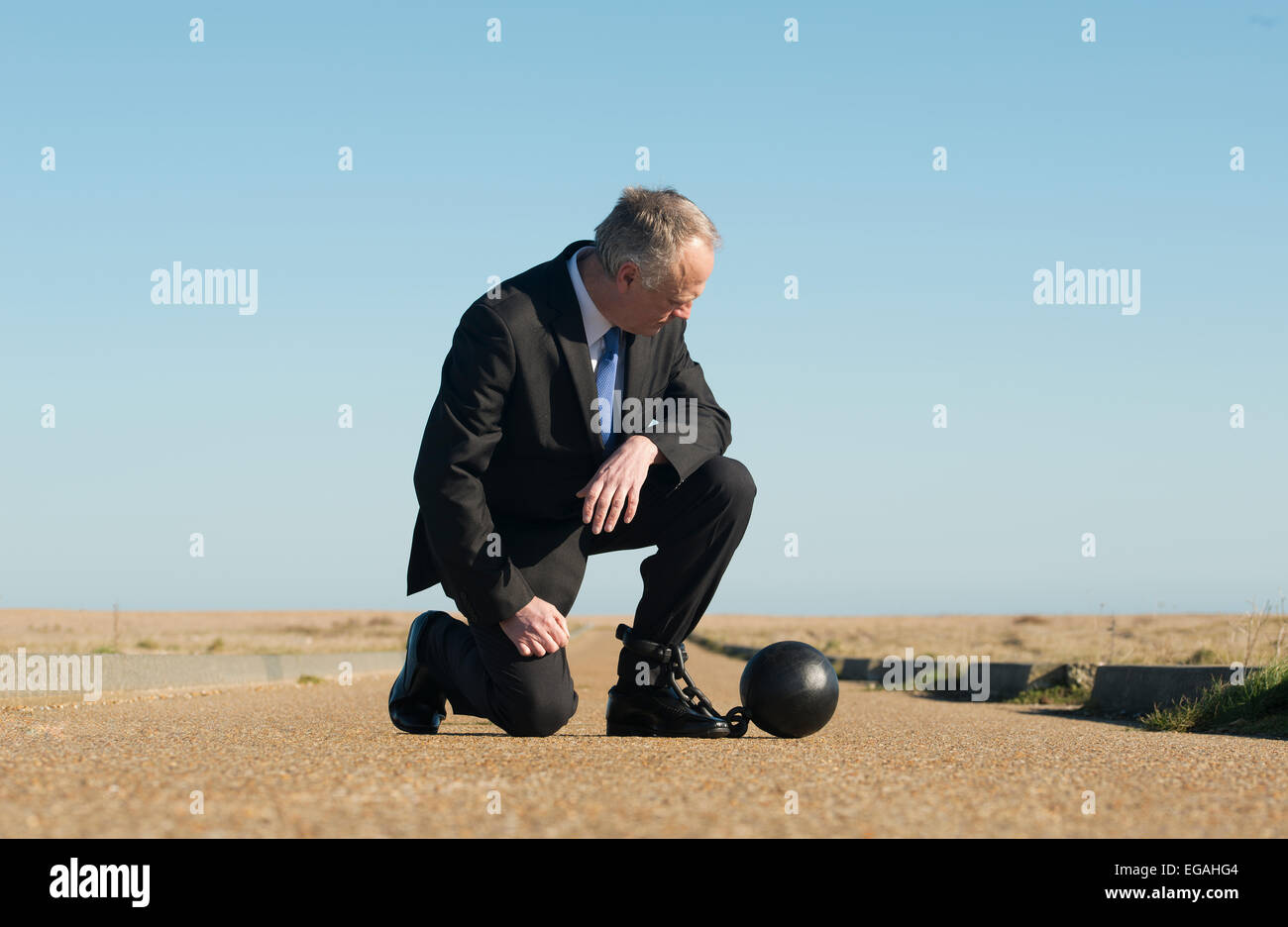 Pensive businessman, kneeling in the middle of a long remote road, attached to a ball & chain against a clear - Stock Image