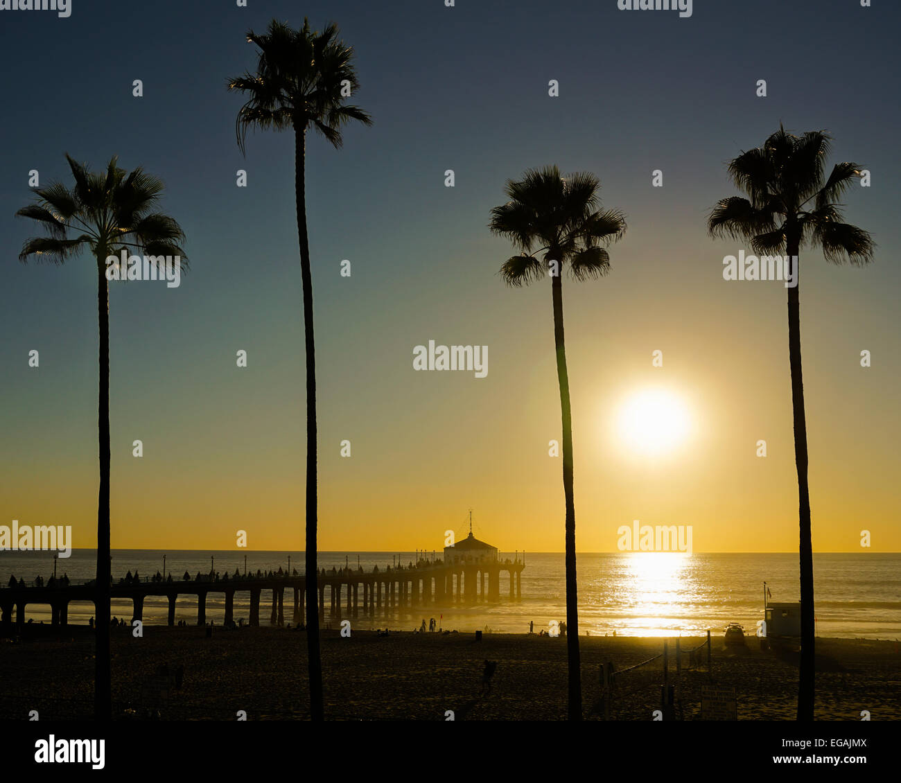 Winter Sunset from Manhattan Beach Pier with silhouette palm trees - Stock Image