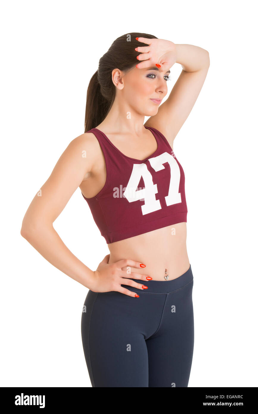 Woman resting after exercising and cleaning up sweat from her forehead, isolated in white Stock Photo