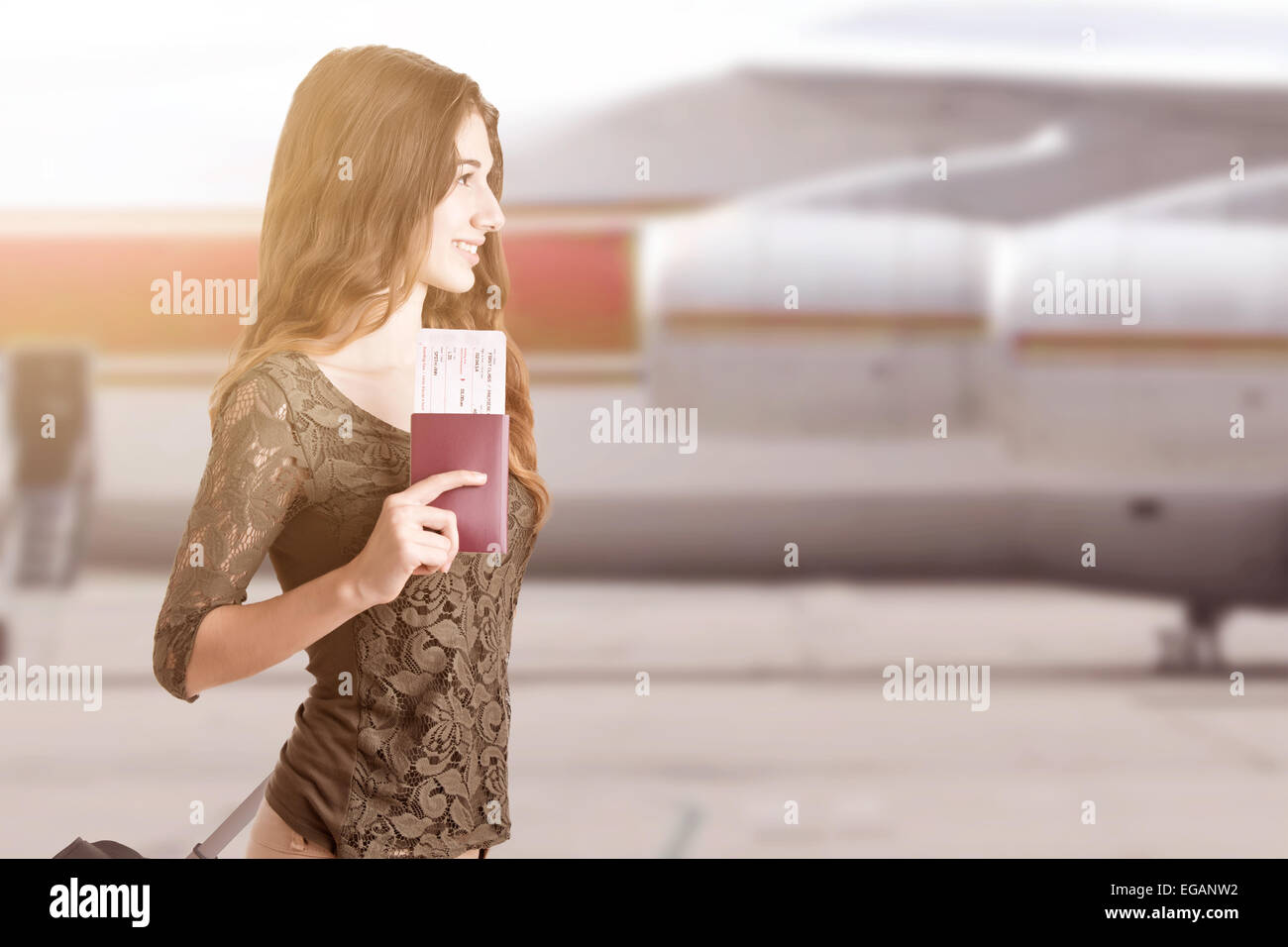 Woman about to board an airplane in an airport runaway at sunset - Stock Image