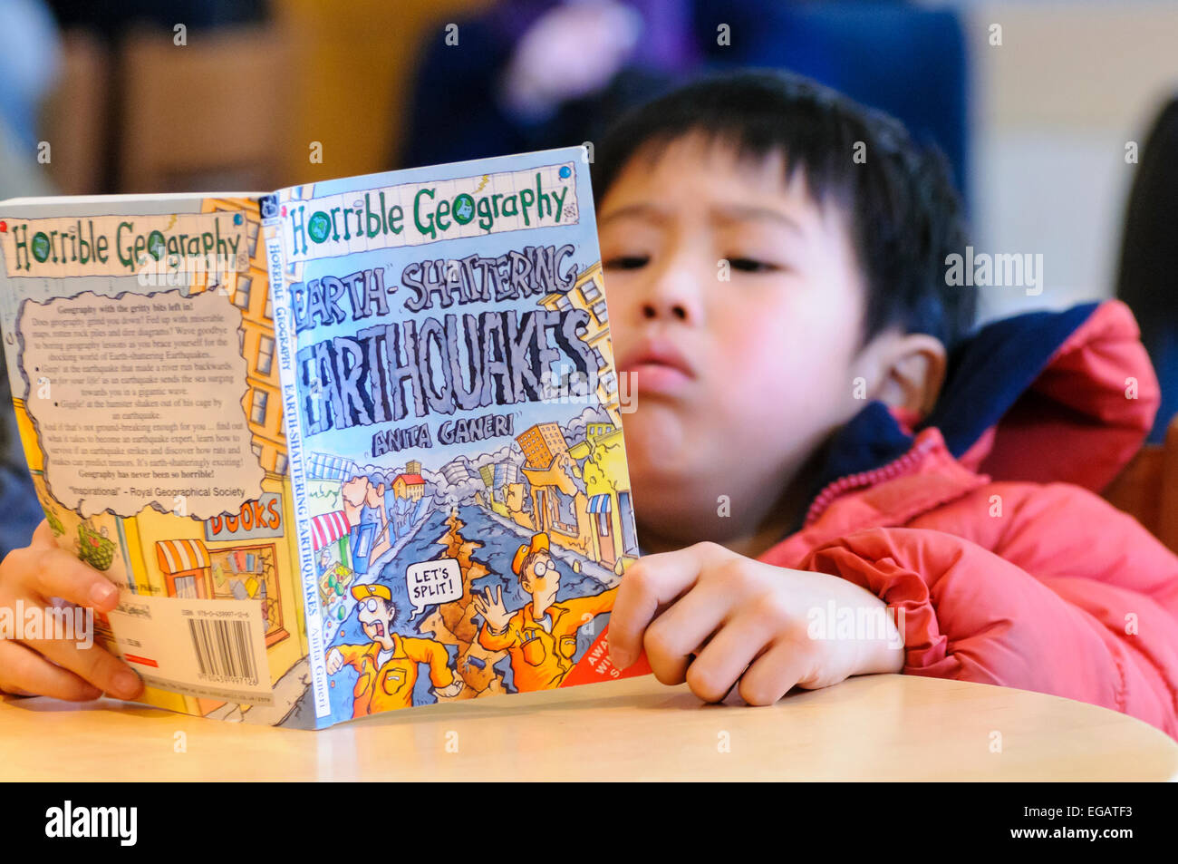 A young Japanese boy reads a book on Earthquakes a few days after the Fukushima disaster - Stock Image