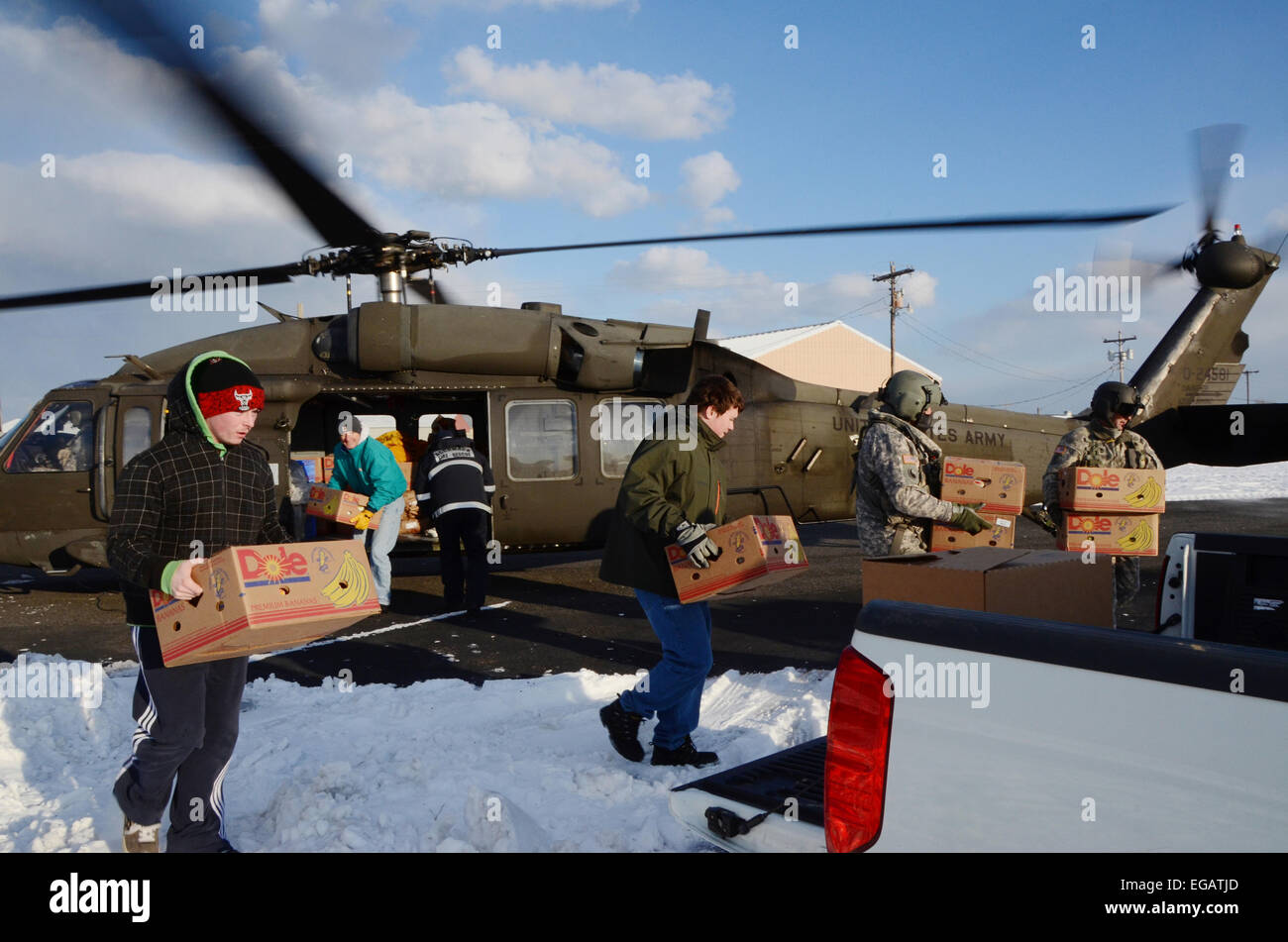 A Virginia Army National Guard aviation crew and residents unload emergency supplies for the residents of  remote - Stock Image