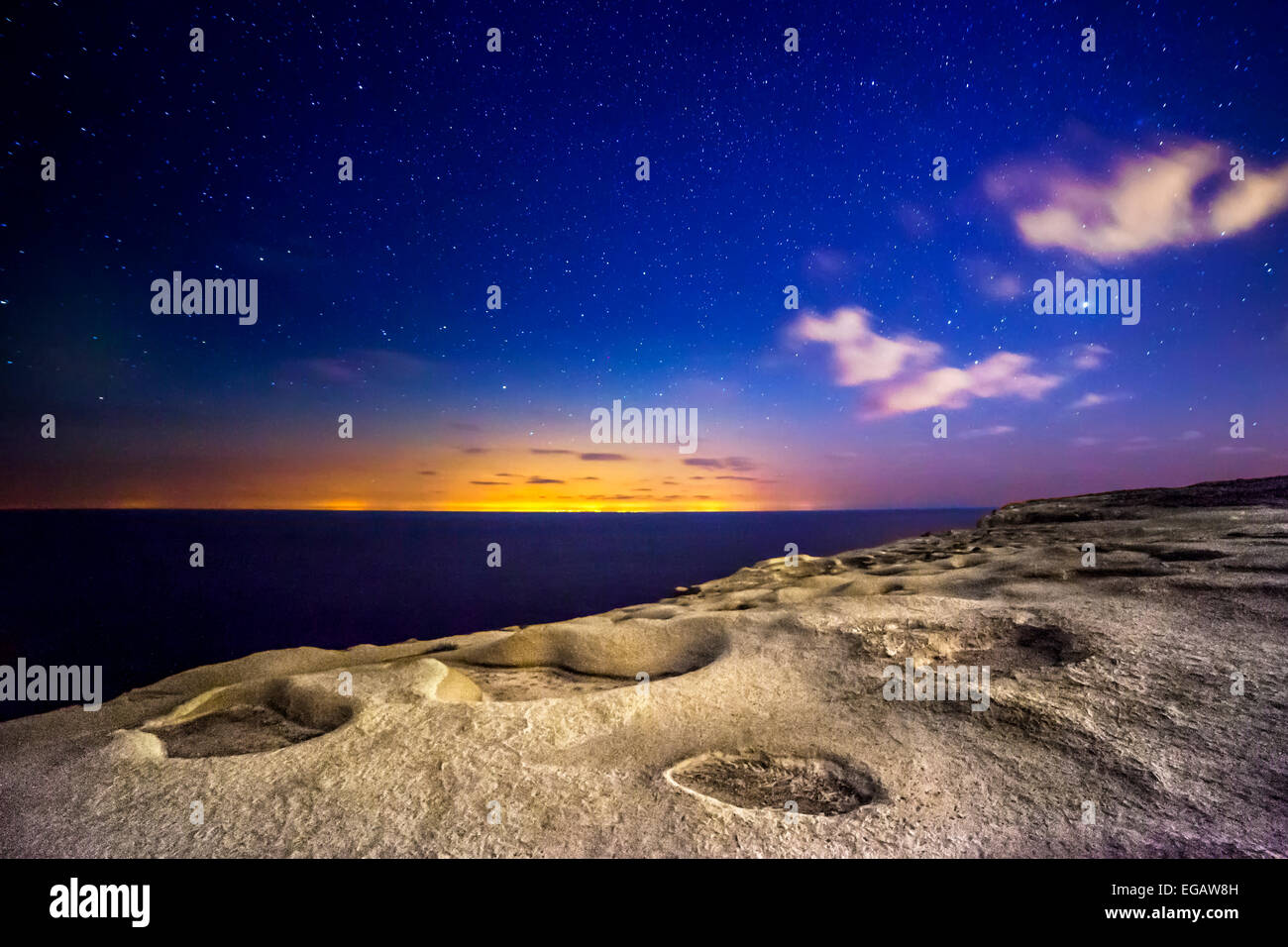 An almost alien and surreal landscape...actually shot on the island of Gozo.  The distant glare and lights are from - Stock Image