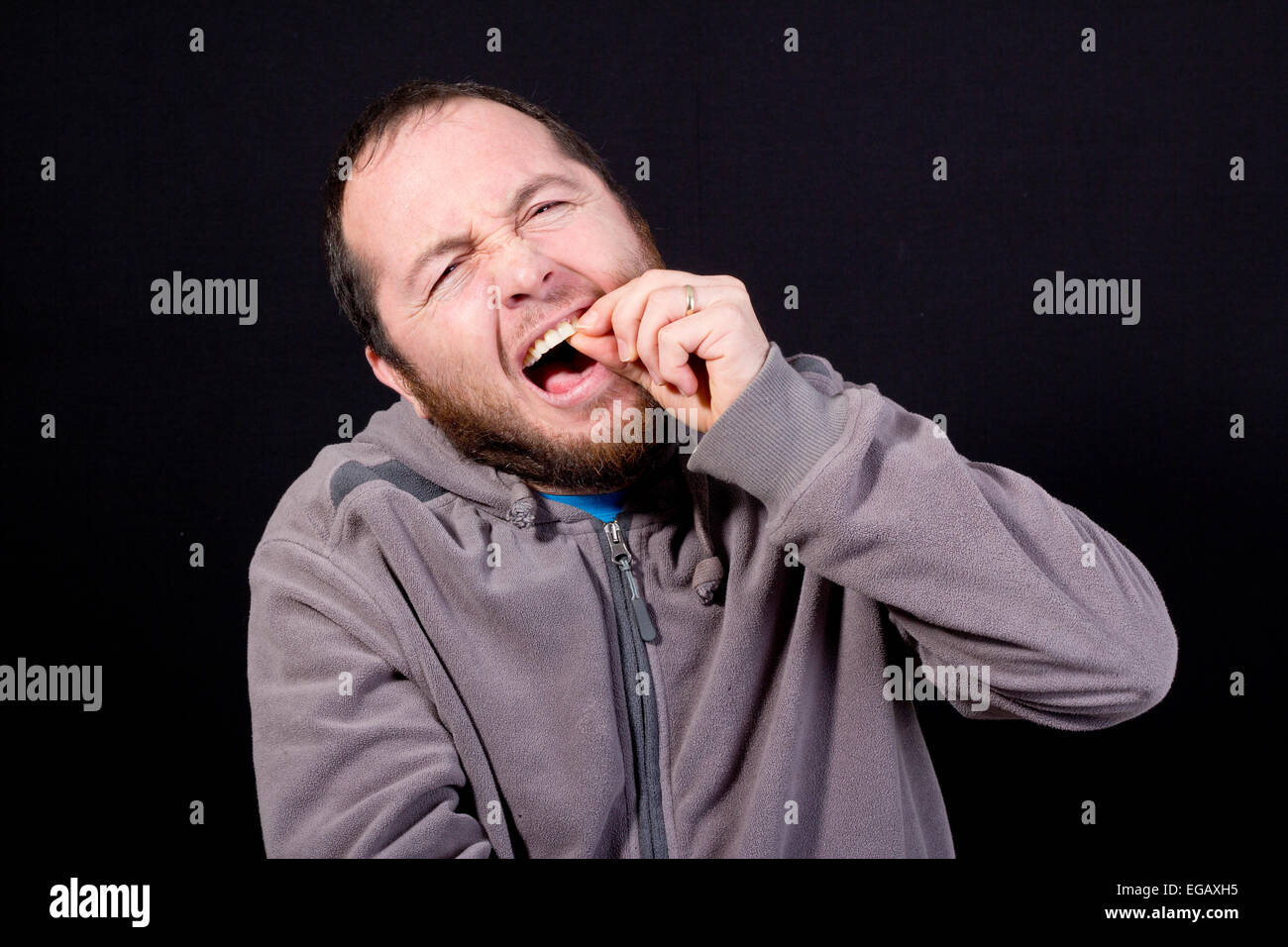man with toothache isolated on black - Stock Image