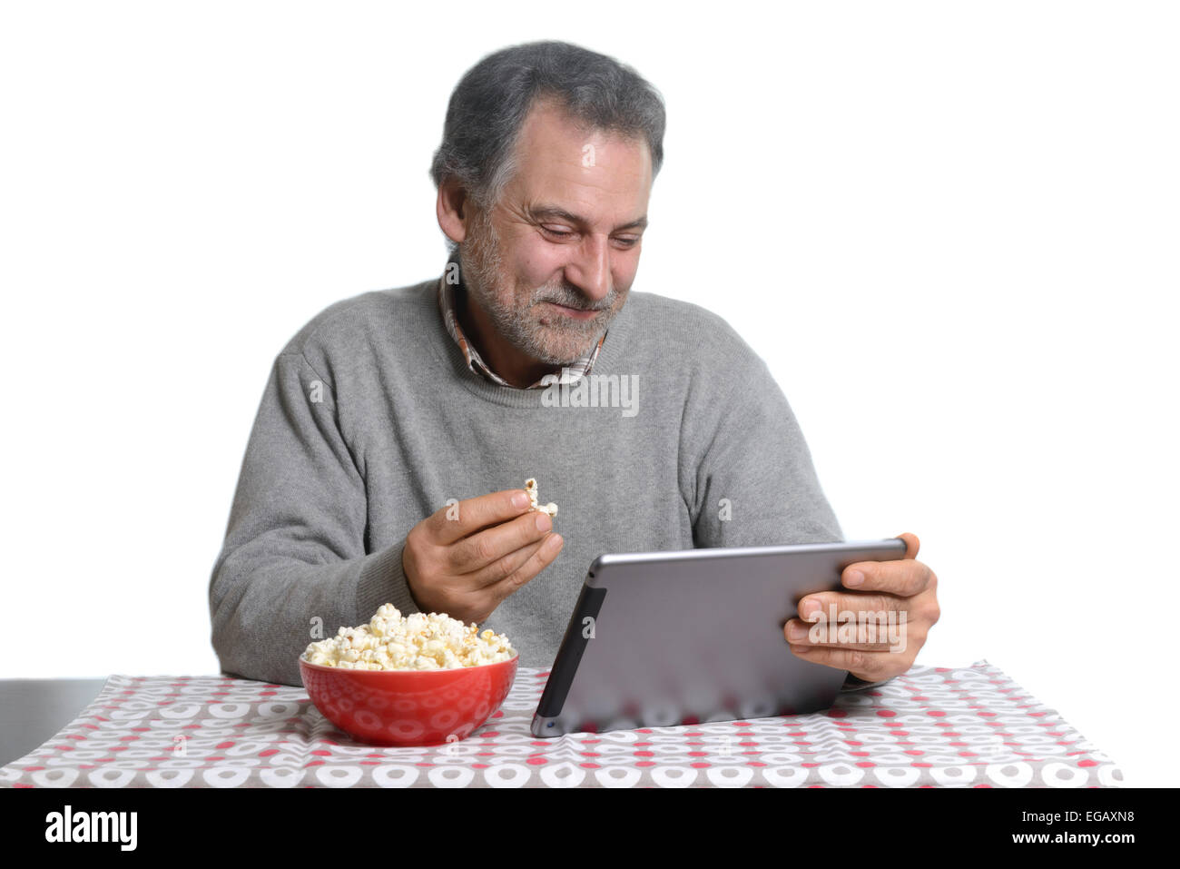 Middle aged man using a tablet computer while eating popcorn at home - Stock Image