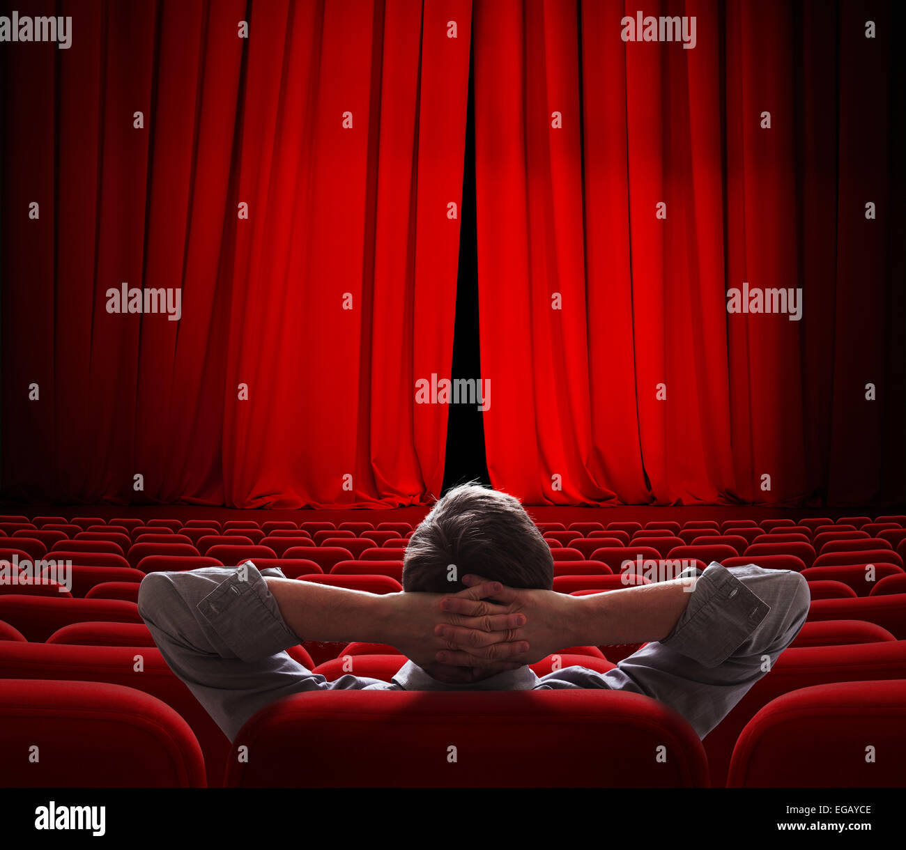 cinema screen red curtains slightly open for vip person - Stock Image