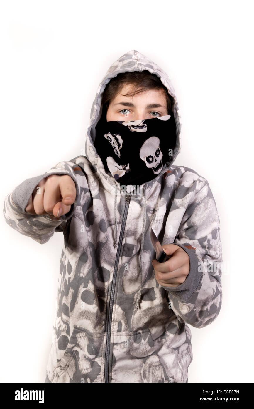 Teenage boy holding a knife acting aggressive - Stock Image
